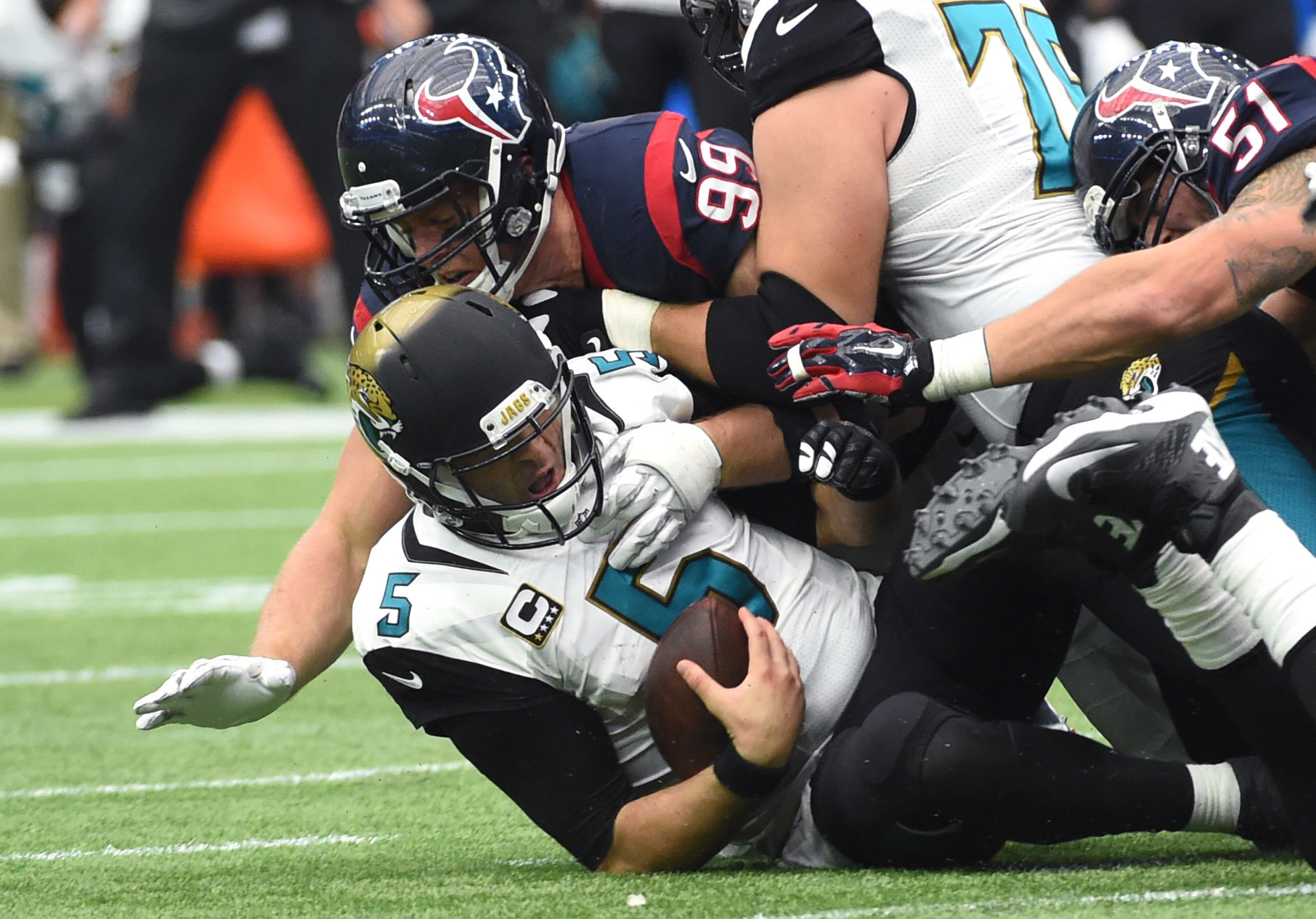 FILE - In this Jan. 3, 2016, file photo, Jacksonville Jaguars quarterback Blake Bortles (5) is sacked by Houston Texans defensive end J.J. Watt (99) during the second half of an NFL football game in Houston. The status of J.J. Watt is uncertain after he m