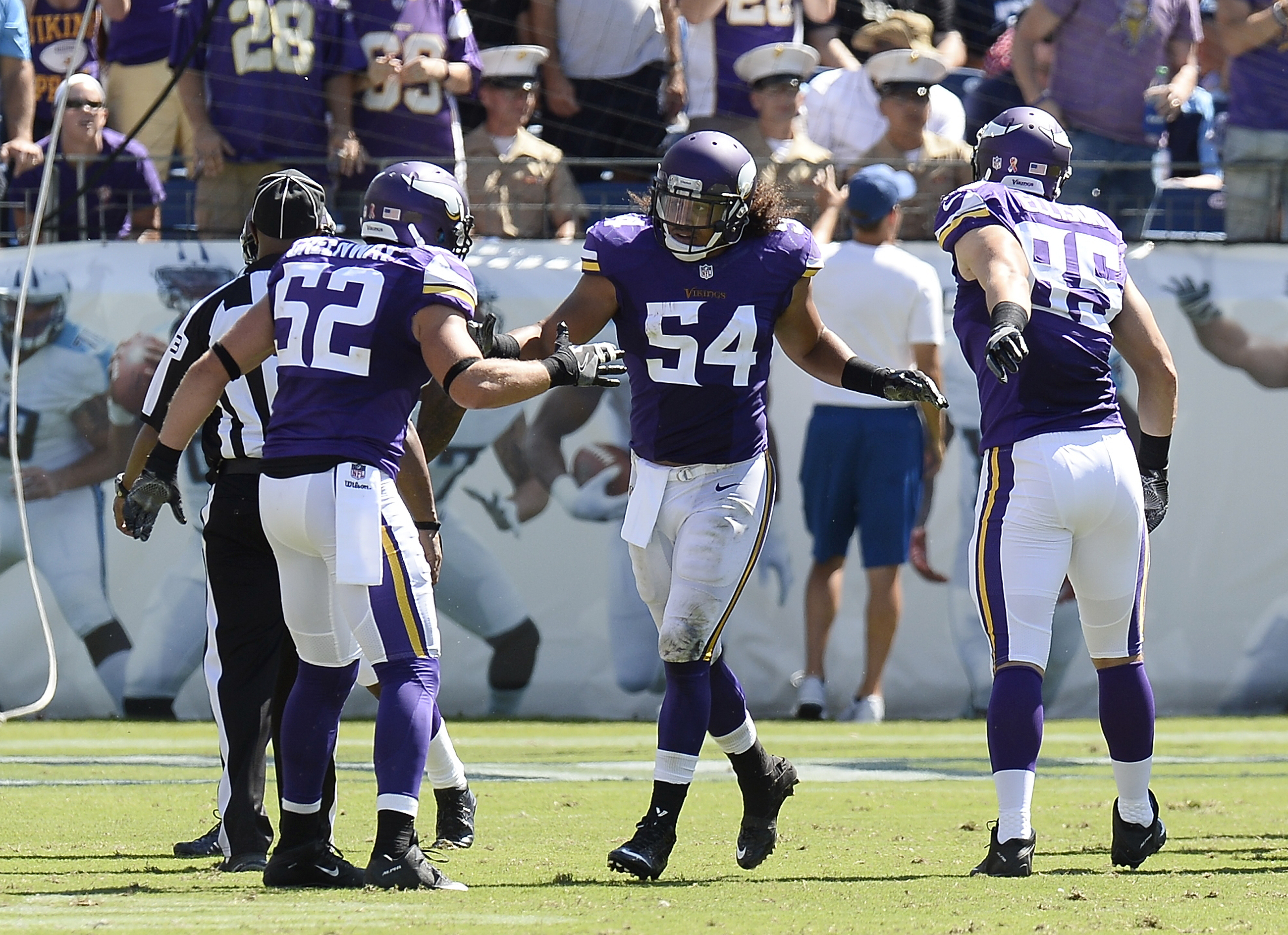Minnesota Vikings linebacker Eric Kendricks (54) is congratulated by Chad Greenway (52) and Rhett Ellison (85) after Kendricks returned an intercepted pass 77 yards for a touchdown against the Tennessee Titans in the second half of an NFL football game Su