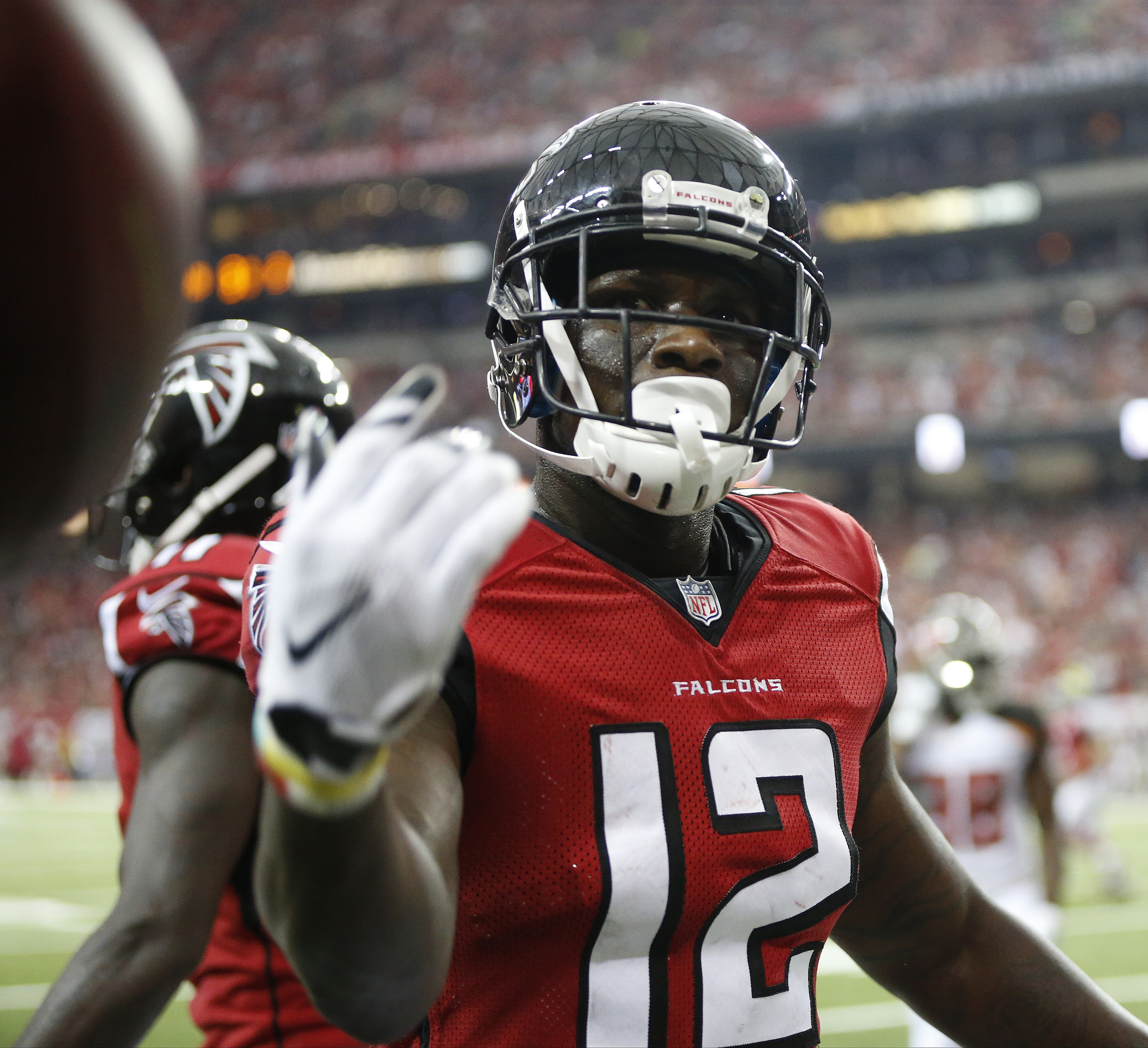 Atlanta Falcons wide receiver Mohamed Sanu (12) tosses the ball to the official after he scored on a two-point conversion against the Tampa Bay Buccaneers during the second half of an NFL football game, Sunday, Sept. 11, 2016, in Atlanta. (AP Photo/John B