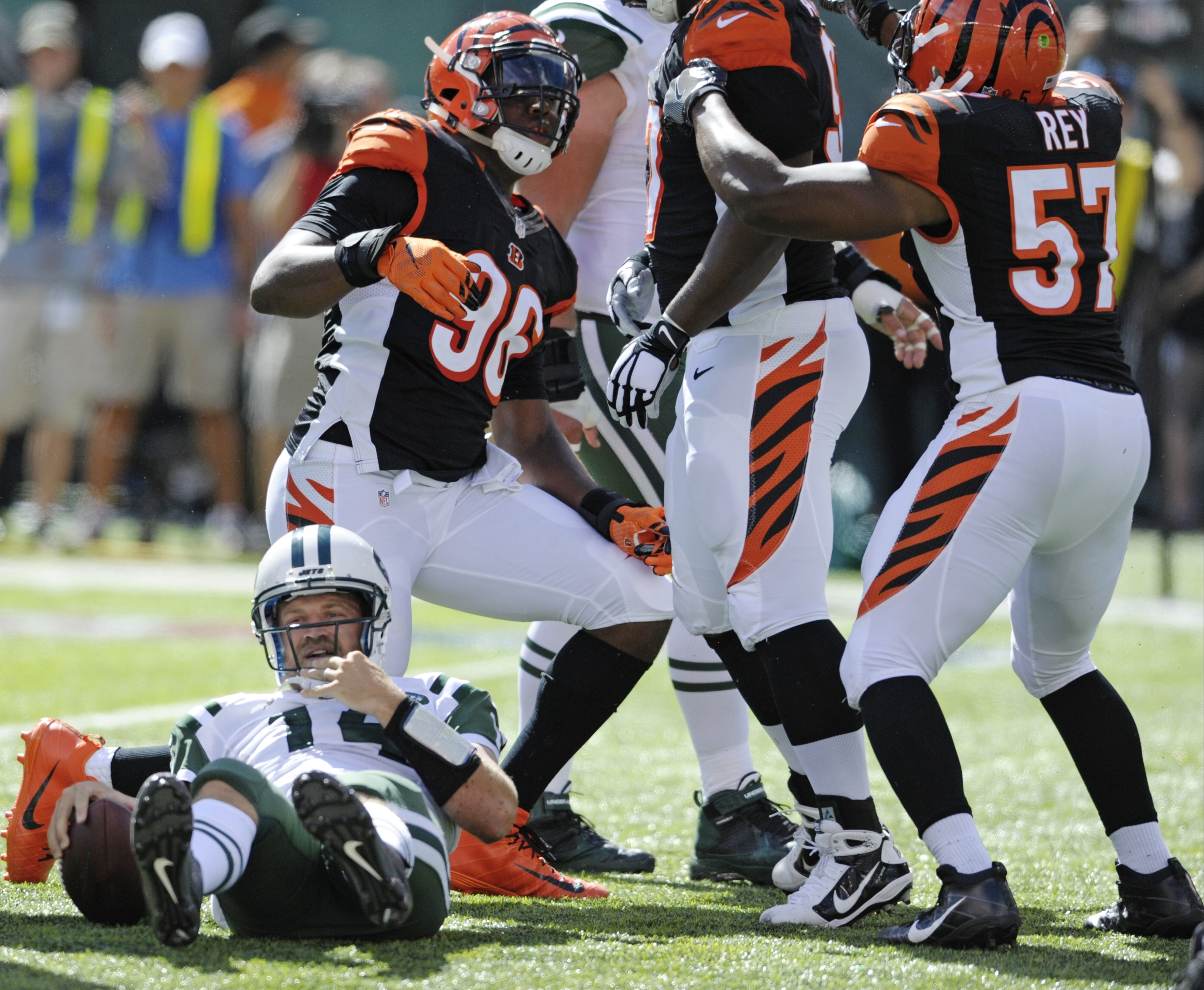 New York Jets quarterback Ryan Fitzpatrick (14) gets up after being sacked as Cincinnati Bengals' Carlos Dunlap (96) celebrates with teammates Geno Atkins, center, and Vincent Rey, (57) during the second half of an NFL football game Sunday, Sept. 11, 2016