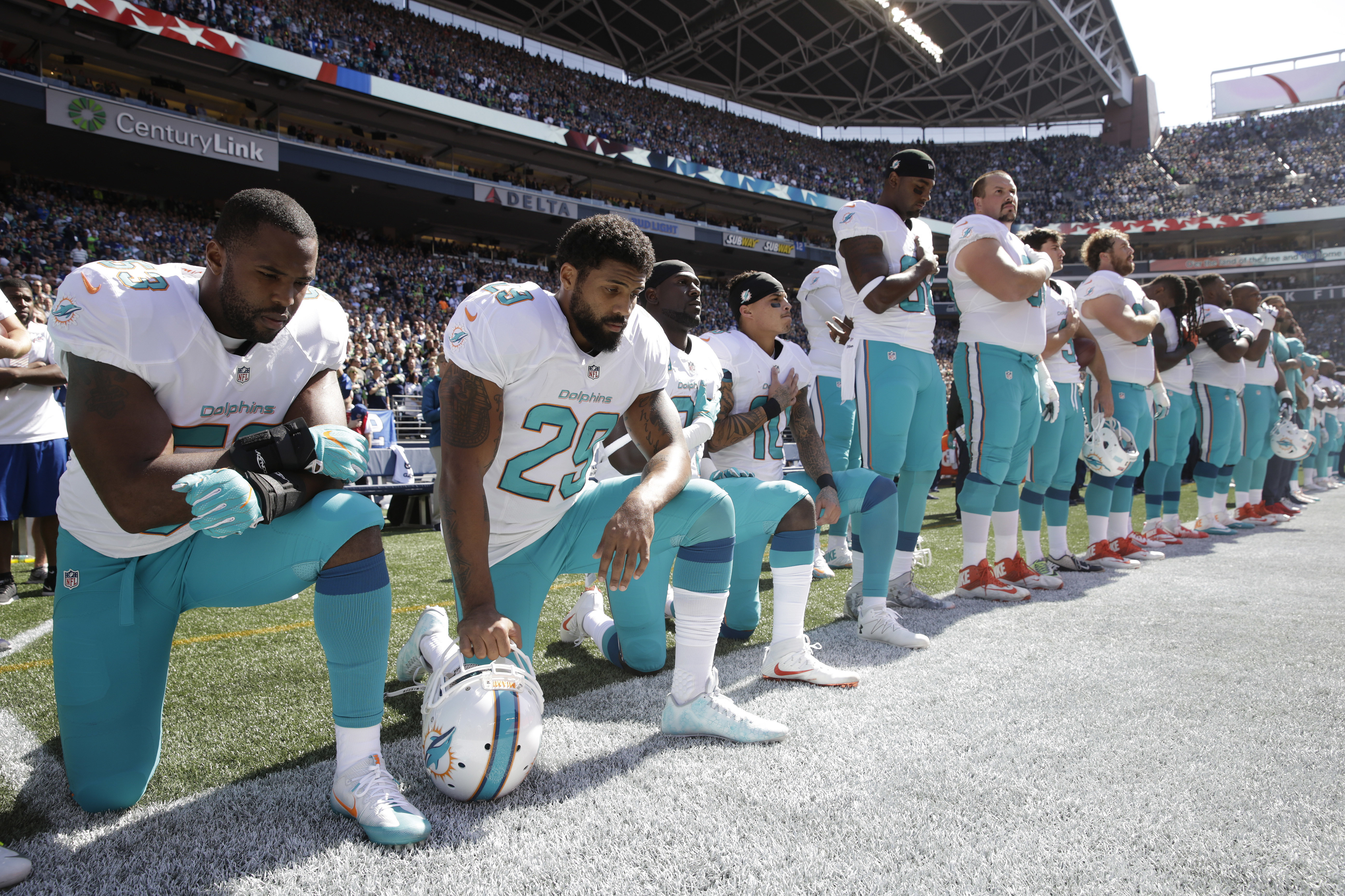 From left, Miami Dolphins' Jelani Jenkins, Arian Foster, Michael Thomas, and Kenny Stills, kneel during the singing of the national anthem before an NFL football game against the Seattle Seahawks, Sunday, Sept. 11, 2016, in Seattle. (AP Photo/Stephen Bras
