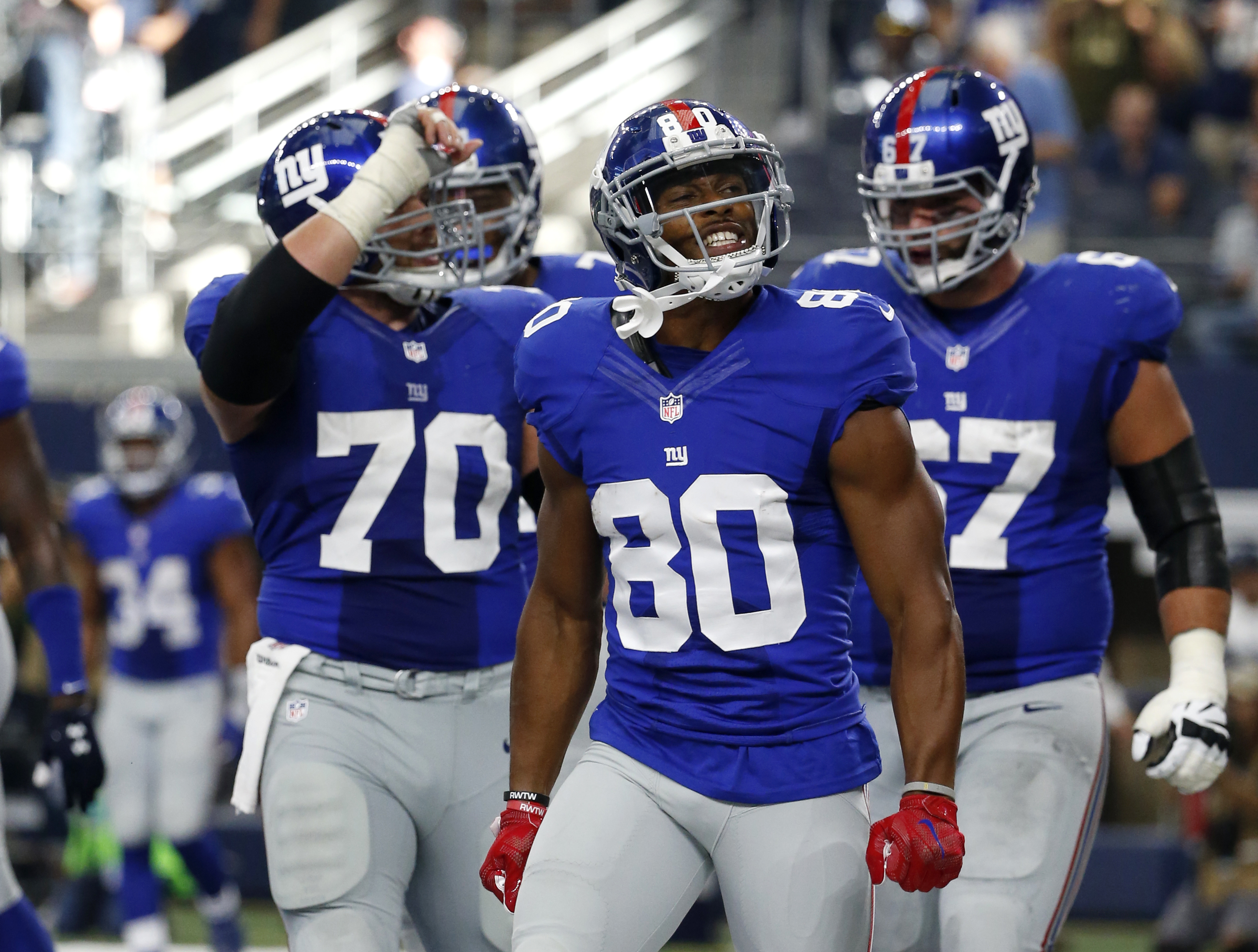 New York Giants center Weston Richburg (70), Victor Cruz (80) and Justin Pugh (67) celebrate a touchdown catch by Victor Cruz (80) in the second half of an NFL football game against the Dallas Cowboys on Sunday Sept. 11, 2016, in Arlington, Texas. (AP Pho