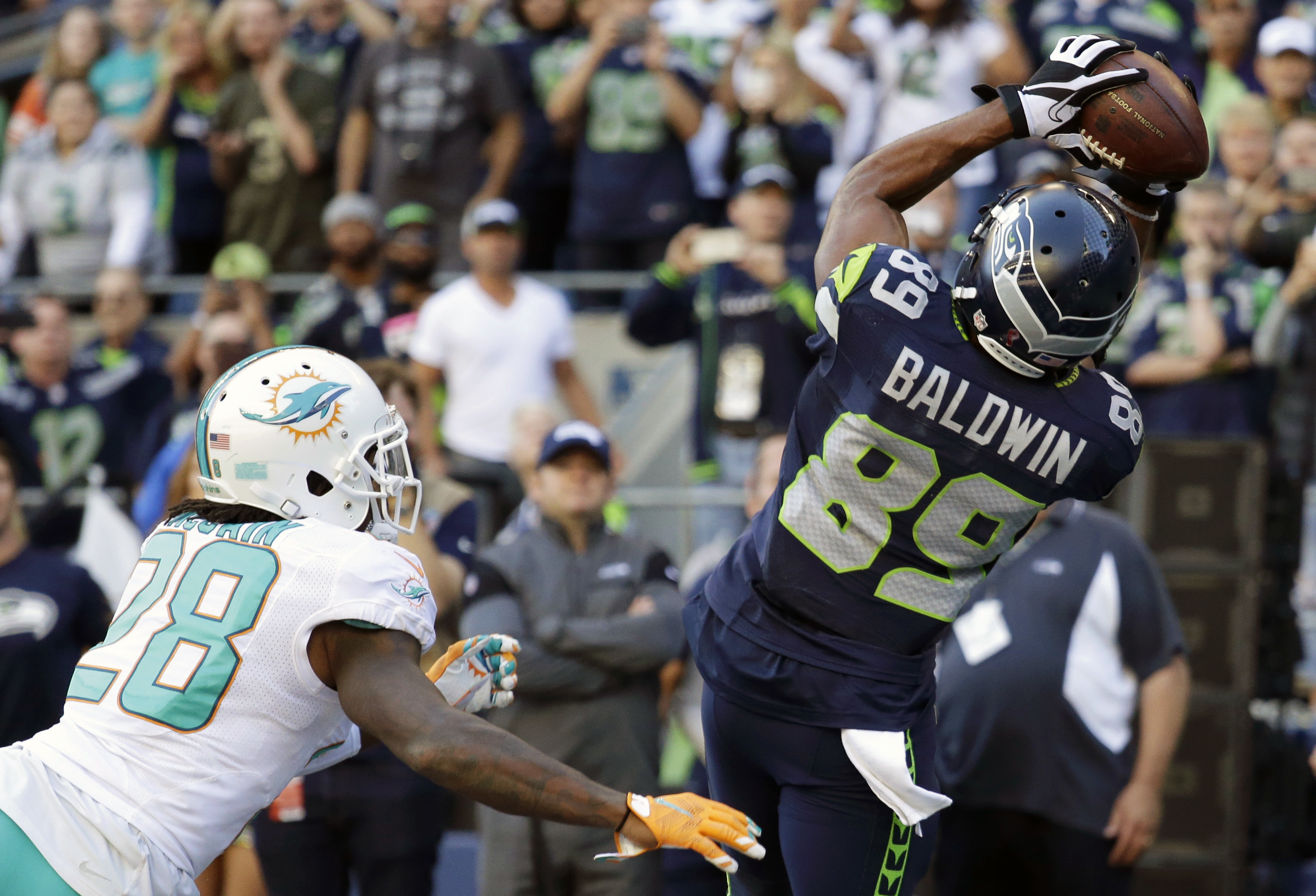 Seattle Seahawks wide receiver Doug Baldwin (89) catches a pass for a touchdown over Miami Dolphins cornerback Bobby McCain (28) in the second half of an NFL football game, Sunday, Sept. 11, 2016, in Seattle. (AP Photo/Elaine Thompson)
