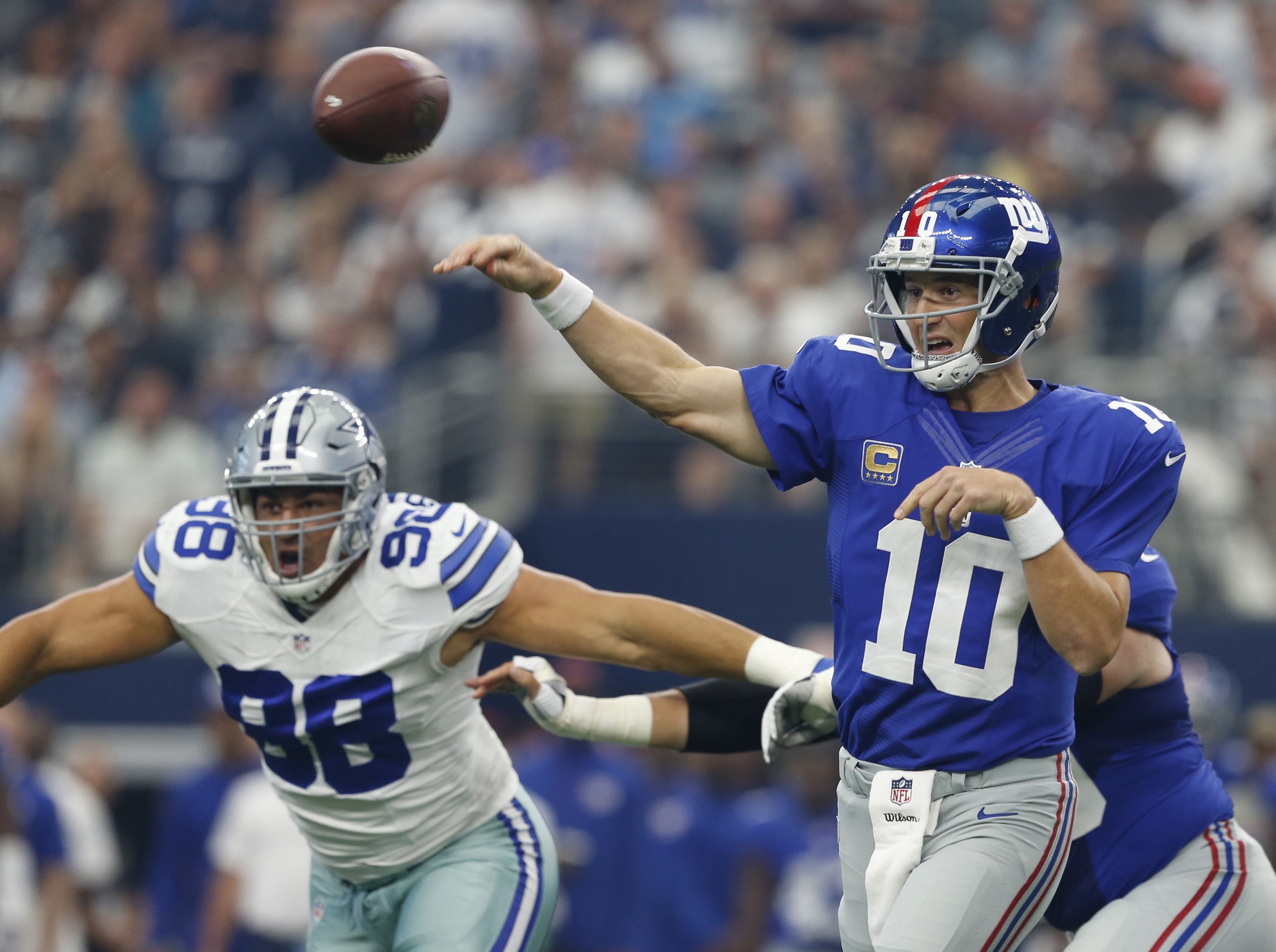 New York Giant quarterback Eli Manning throws down field as Dallas Cowboy's Tyrone Crawford defends during the first half of an NFL football game at AT&T Stadium, Sunday, Sept. 11, 2016, in Arlington, Texas. (Jose Yau/Waco Tribune Herald via AP)