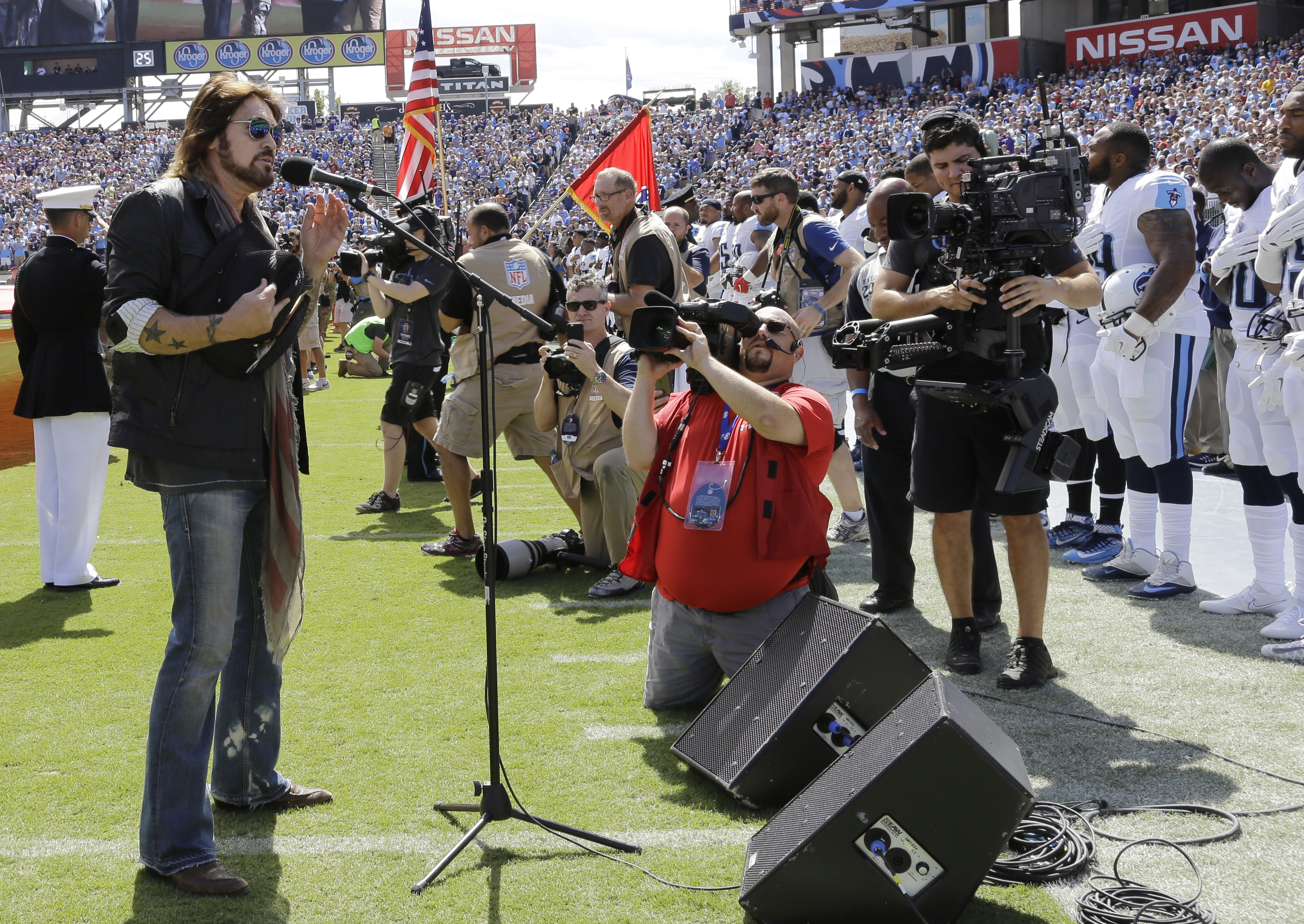 FILE - In this Sept. 11, 2016, file photo, Tennessee Titans players, including Wesley Woodyard, far right, Jason McCourty, second from right, and Jurrell Casey, third from right, stand during the singing of the national anthem by Billy Ray Cyrus, left, be