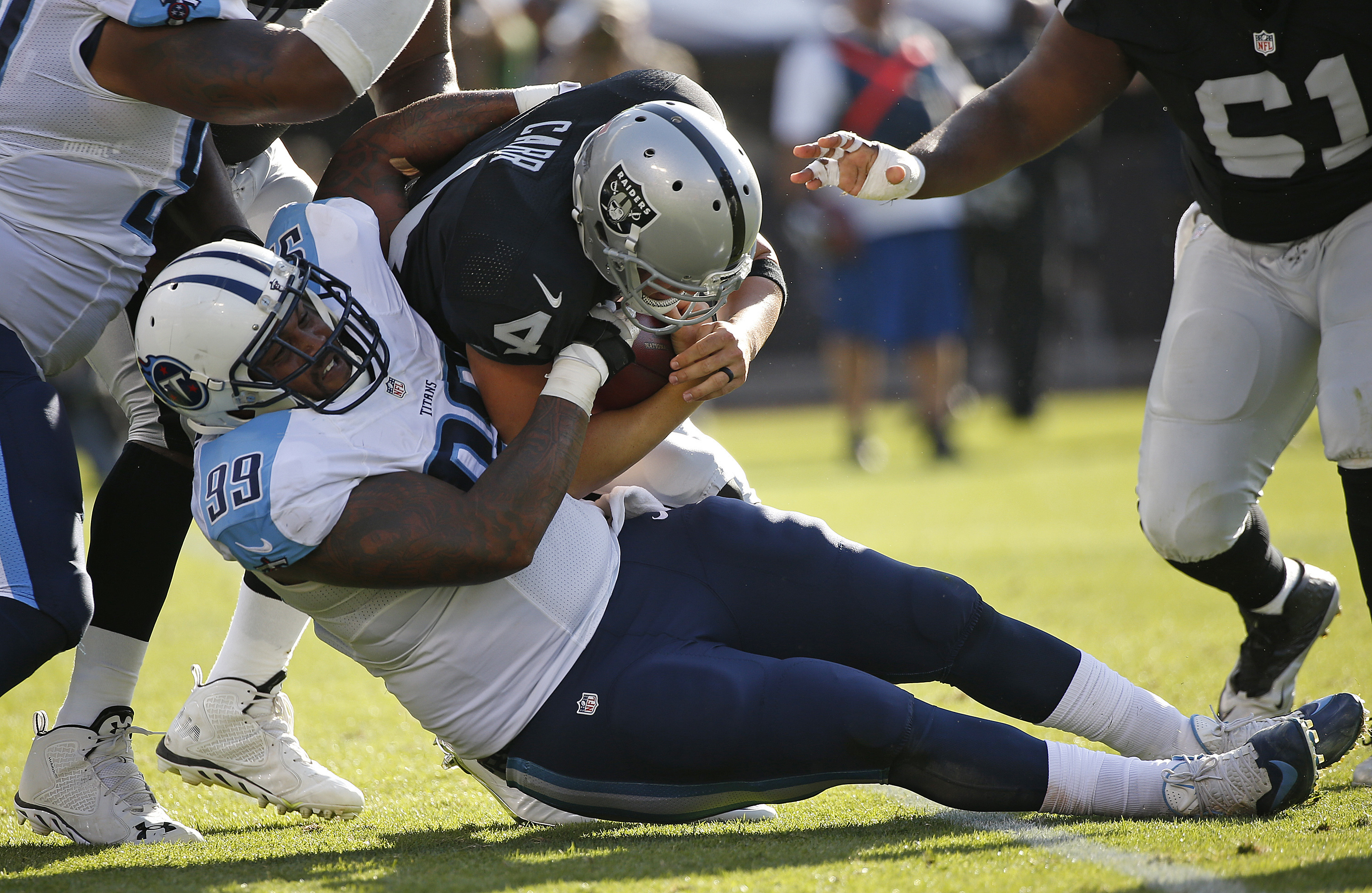 FILE - In this Aug. 27, 2016, file photo, Oakland Raiders quarterback Derek Carr is sacked by Tennessee Titans defensive end Jurrell Casey (99) during the first half of an NFL preseason football game, in Oakland, Calif.  The Titans got close to Shaun Hill