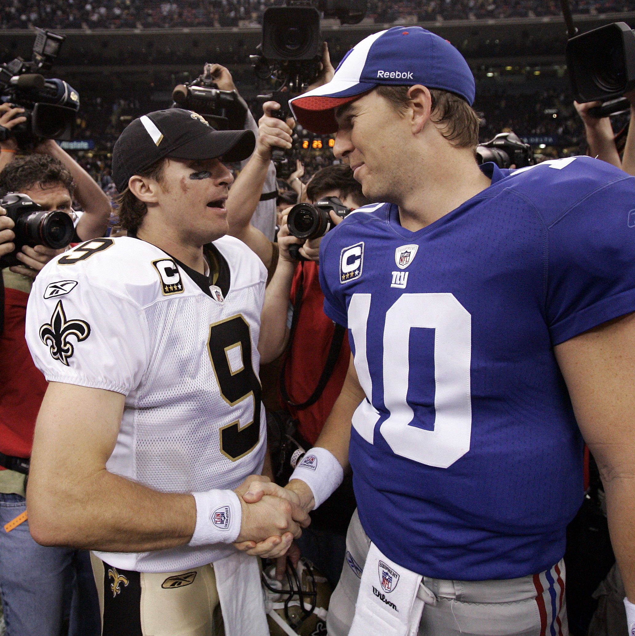 FILE - In this Oct. 18, 2009, file photo, New Orleans Saints quarterback Drew Brees (9) and New York Giants quarterback Eli Manning (10) shake hands after an NFL football game in New Orleans. Brees and Manning are friends off the field and rivals on the f
