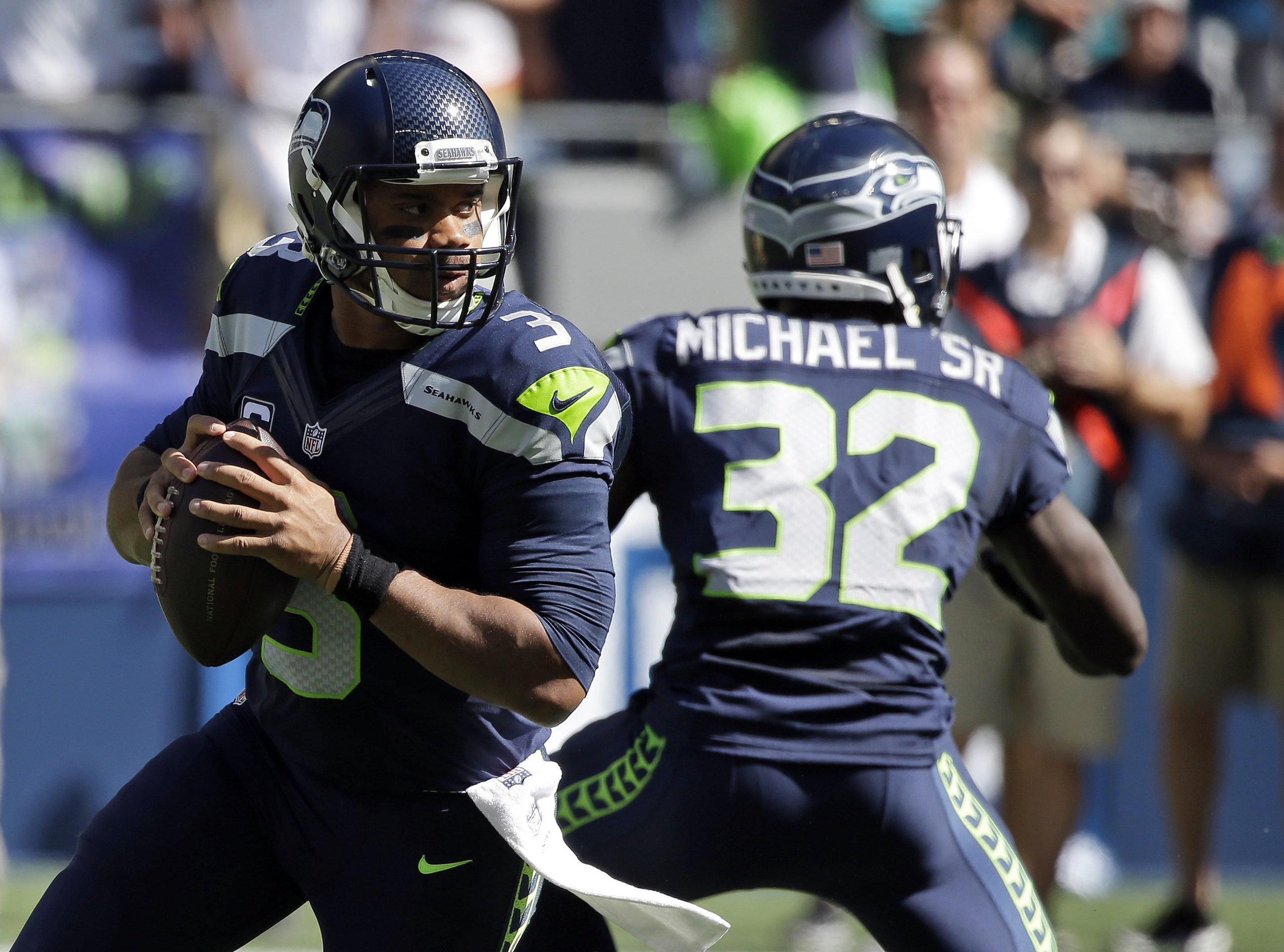 FILE - In this Sunday, Sept. 11, 2016, file photo, Seattle Seahawks quarterback Russell Wilson, left, drops to pass against the Miami Dolphins in the first half of an NFL football game in Seattle. Wilson insists he'll be ready to play against the Los Ange