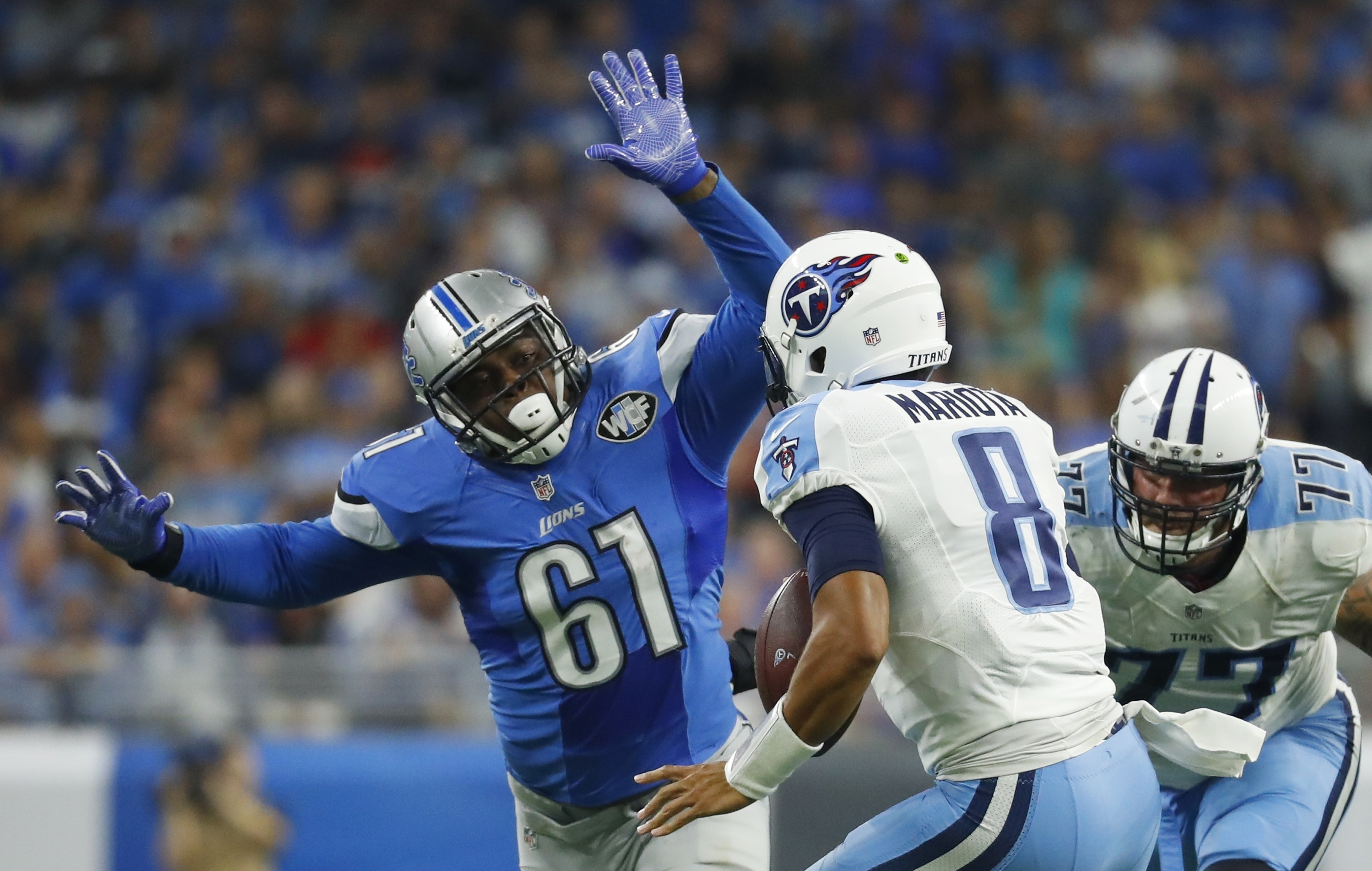 Detroit Lions defensive end Kerry Hyder (61) chases Tennessee Titans quarterback Marcus Mariota (8) during the first half of an NFL football game, Sunday, Sept. 18, 2016, in Detroit. (AP Photo/Paul Sancya)