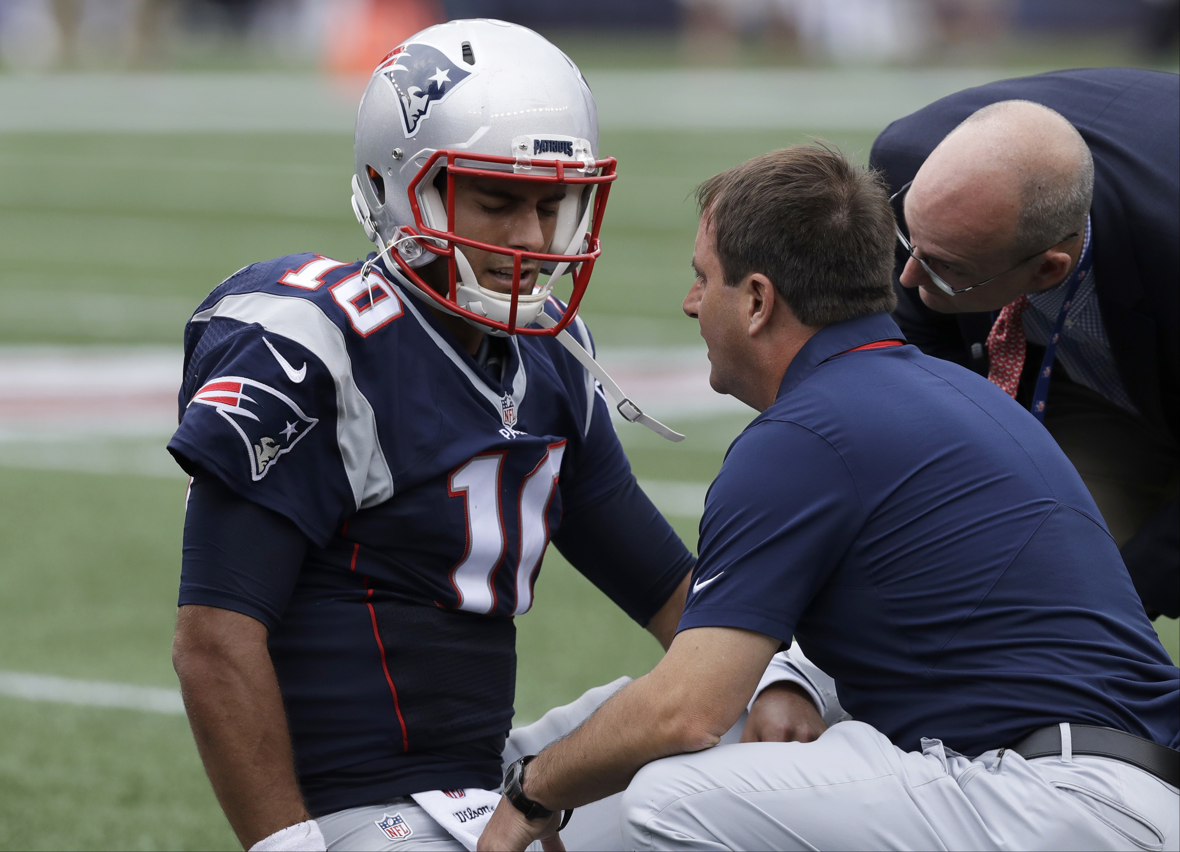 New England Patriots quarterback Jimmy Garoppolo receives attention after an injury during the first half of an NFL football game against the Miami Dolphins, Sunday, Sept. 18, 2016, in Foxborough, Mass. (AP Photo/Charles Krupa)
