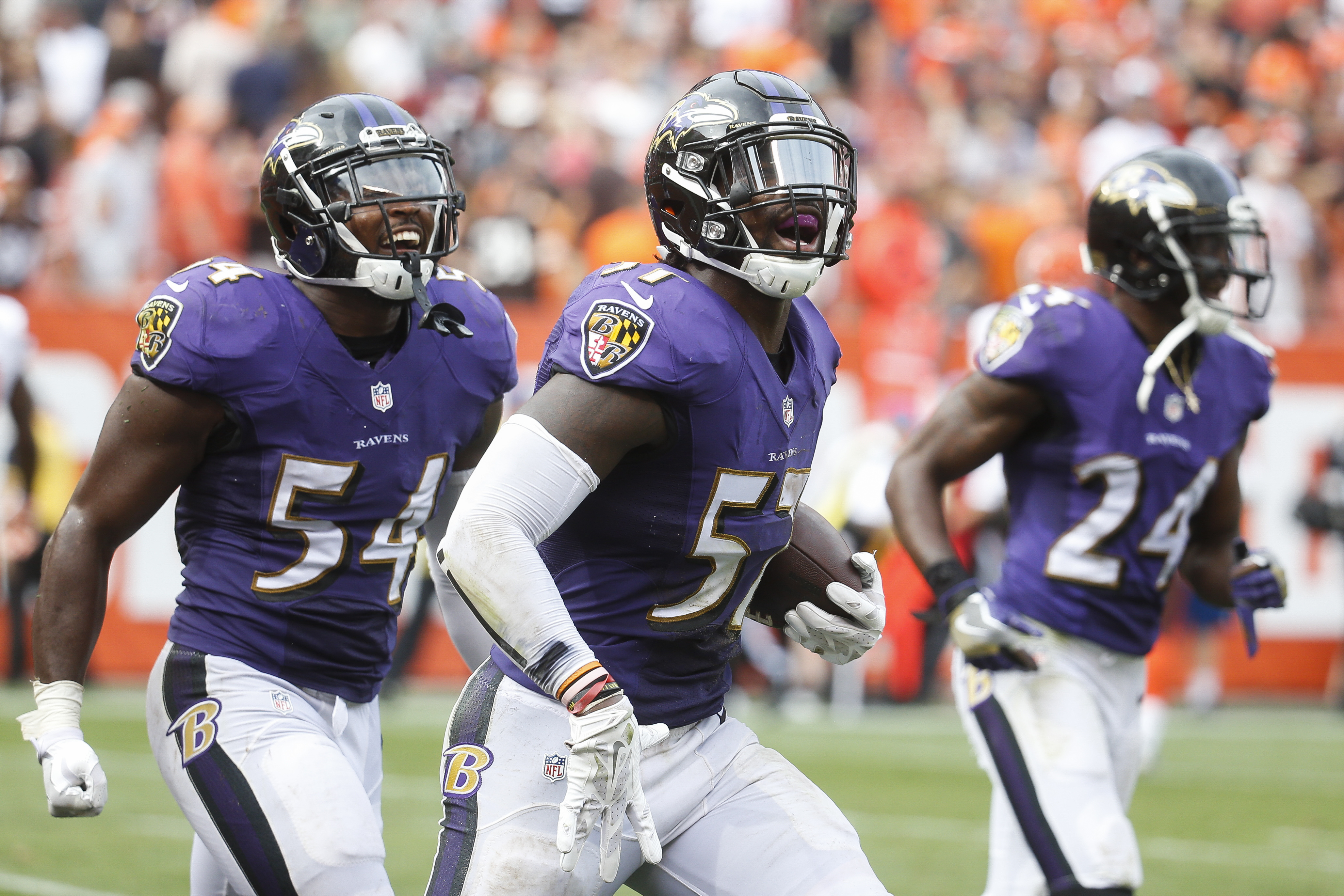 Baltimore Ravens inside linebacker C.J. Mosley, center, celebrates alongside inside linebacker Zach Orr (54) and cornerback Shareece Wright (24) after catching an interception in the final seconds of the second half of an NFL football game against the Cle