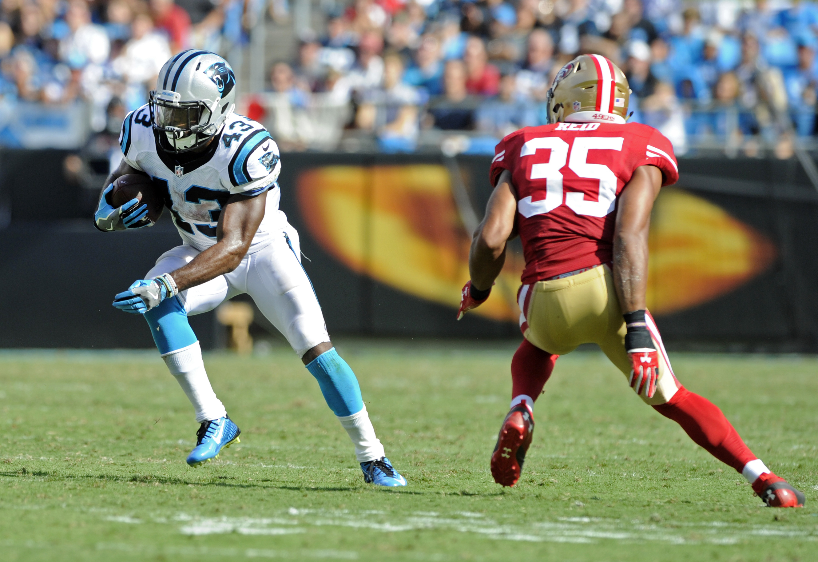 Carolina Panthers' Fozzy Whittaker (43) runs past San Francisco 49ers' Eric Reid (35) in the second half of an NFL football game in Charlotte, N.C., Sunday, Sept. 18, 2016. (AP Photo/Mike McCarn)