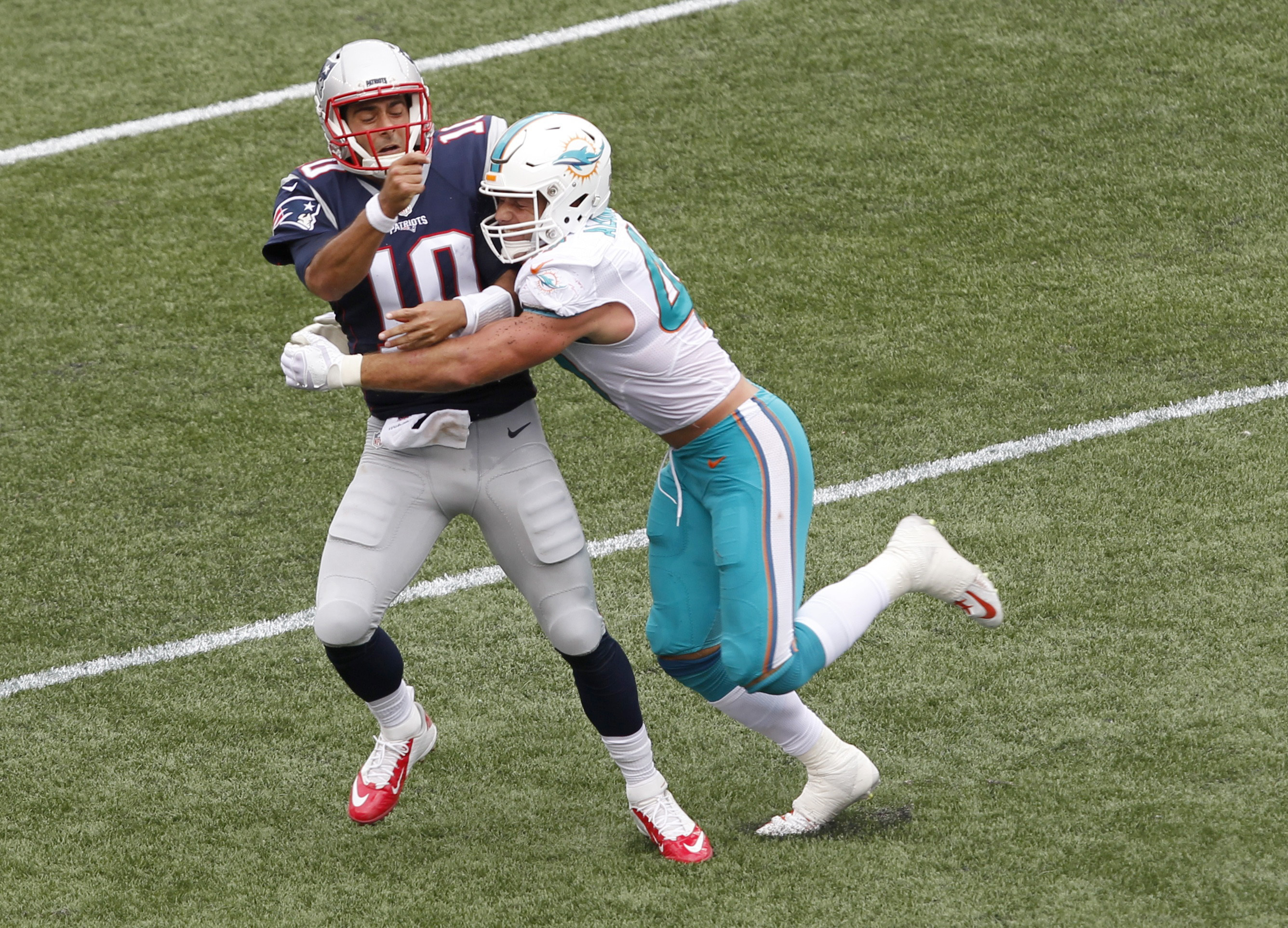 Miami Dolphins linebacker Kiko Alonso, right, hits New England Patriots quarterback Jimmy Garoppolo (10) after he threw a pass during the first half of an NFL football game Sunday, Sept. 18, 2016, in Foxborough, Mass. Garoppolo was injured on the play and