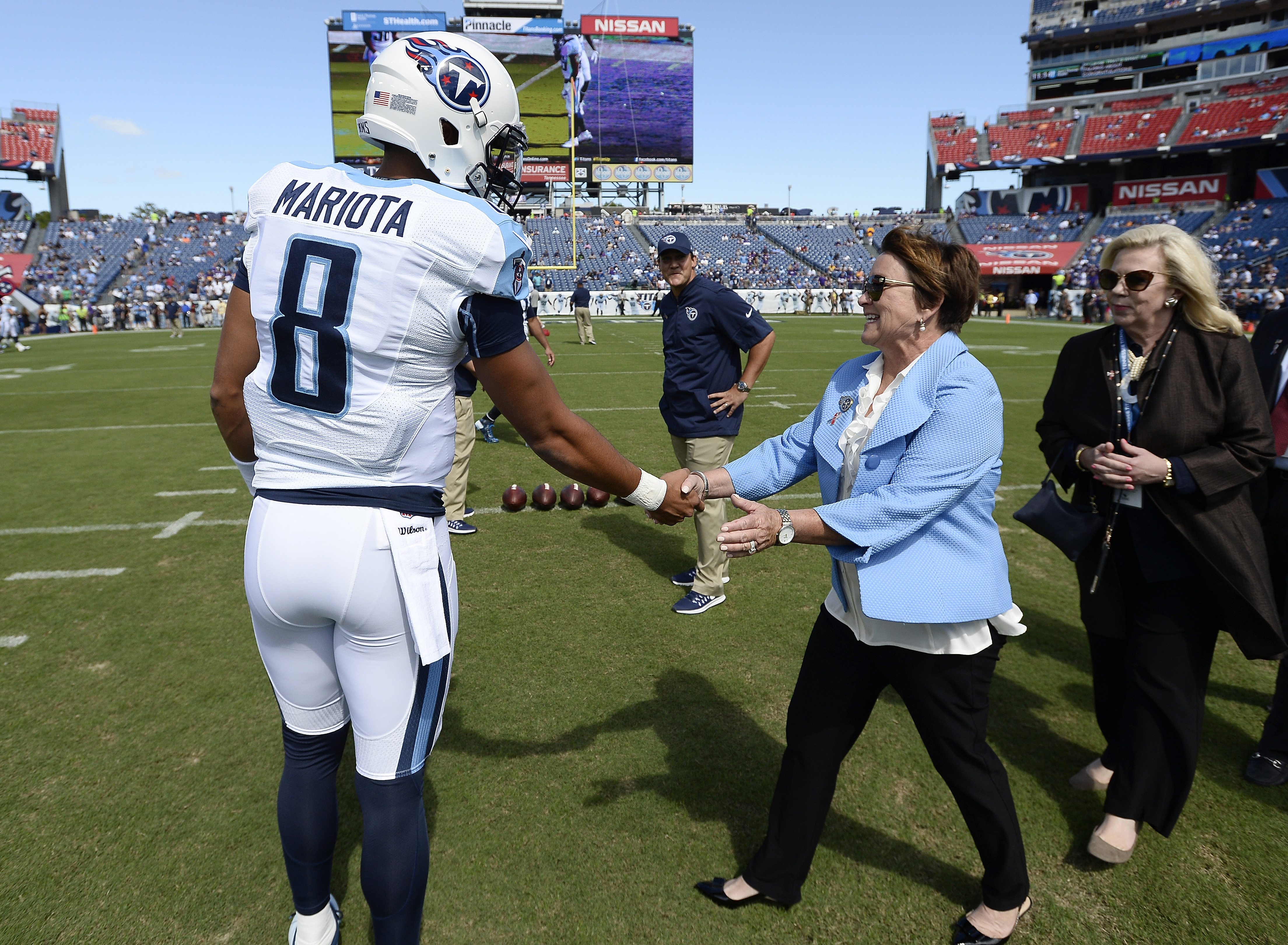FILE - In this Sept. 11, 2016, file photo, Tennessee Titans quarterback Marcus Mariota (8) greets Titans owner Amy Adams Strunk, center, before an NFL football game against the Minnesota Vikings, in Nashville, Tenn. The NFL slapped Tennessees ownership wi