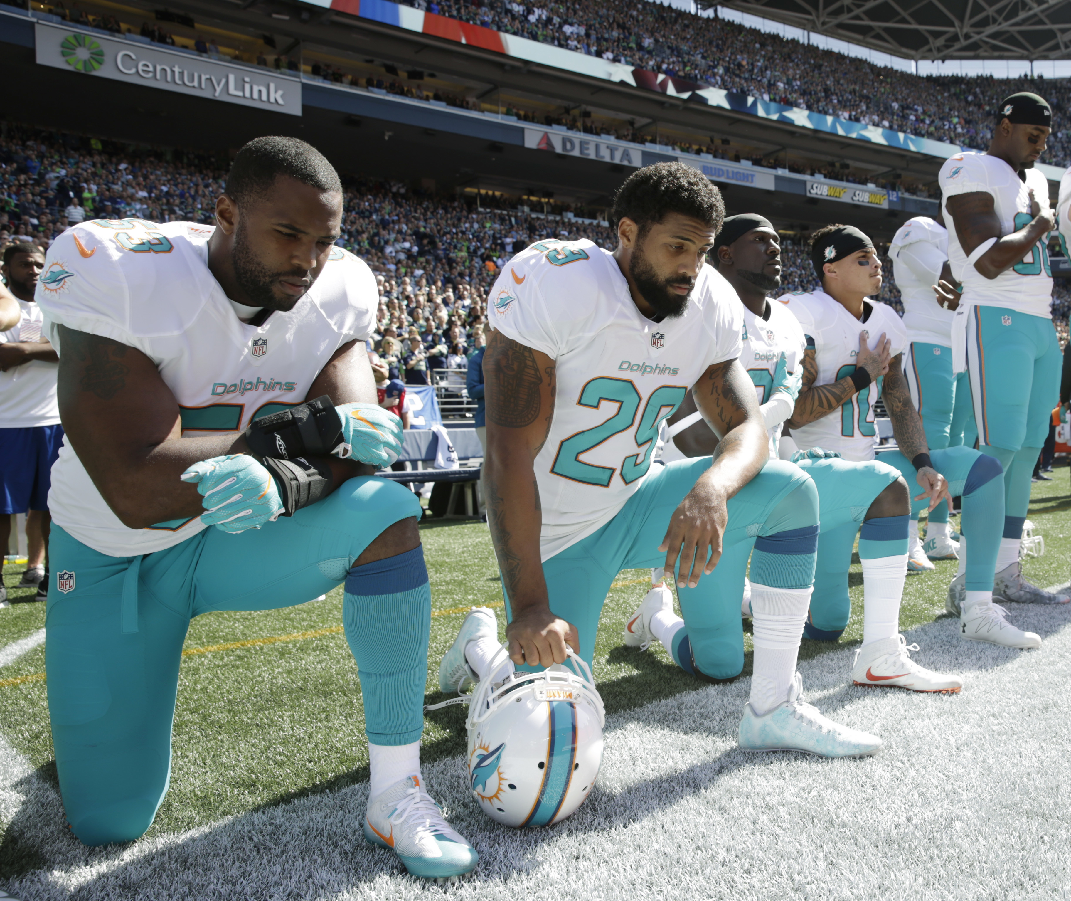 FILE - In this Sept. 11, 2016, file photo, from left, Miami Dolphins' Jelani Jenkins, Arian Foster, Michael Thomas, and Kenny Stills kneel during the singing of the national anthem before an NFL football game against the Seattle Seahawks in Seattle. Miami