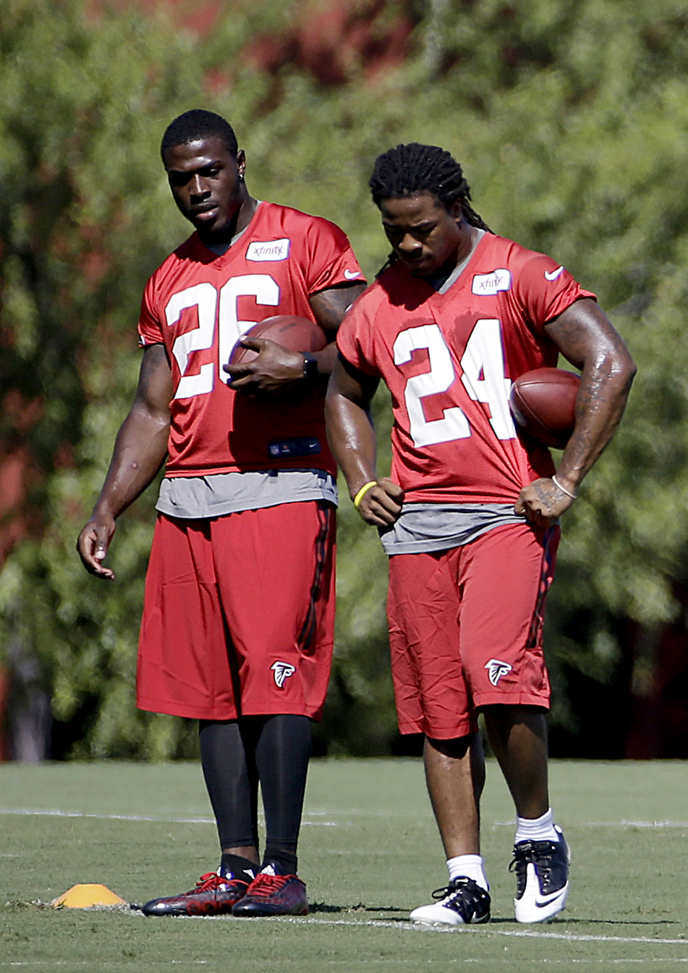 FILE - In this Aug. 12, 2015, file photo, Atlanta Falcons' Tevin Coleman, left, and Devonta Freeman walk on the field during NFL football training camp in Flowery Branch, Ga. Second-year running back Tevin Coleman has played a bigger role through two game