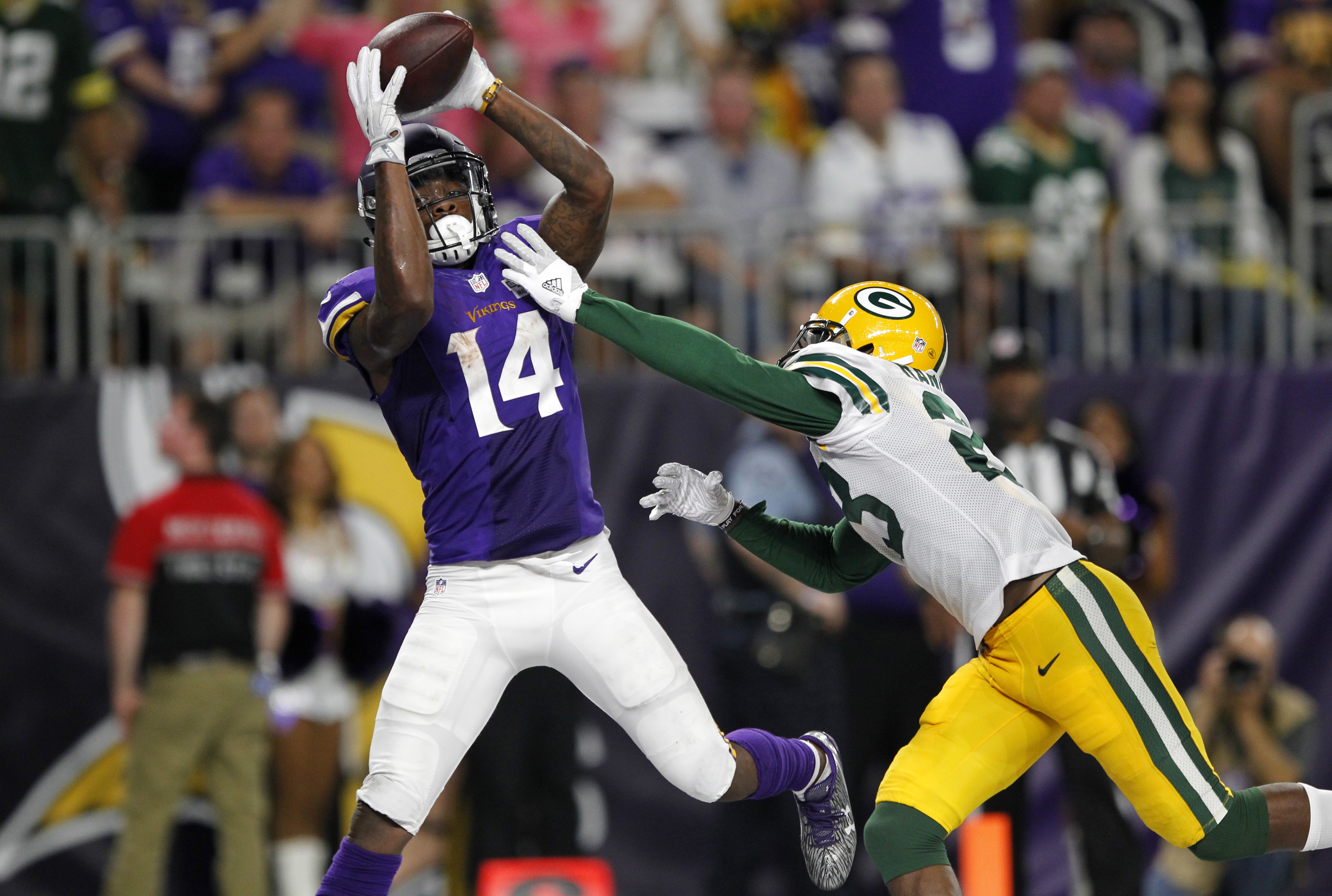 FILE - In this Sunday, Sept. 18, 2016, file photo, Minnesota Vikings wide receiver Stefon Diggs (14) catches a 25-yard touchdown pass over Green Bay Packers cornerback Damarious Randall, right, during the second half of an NFL football game in Minneapolis