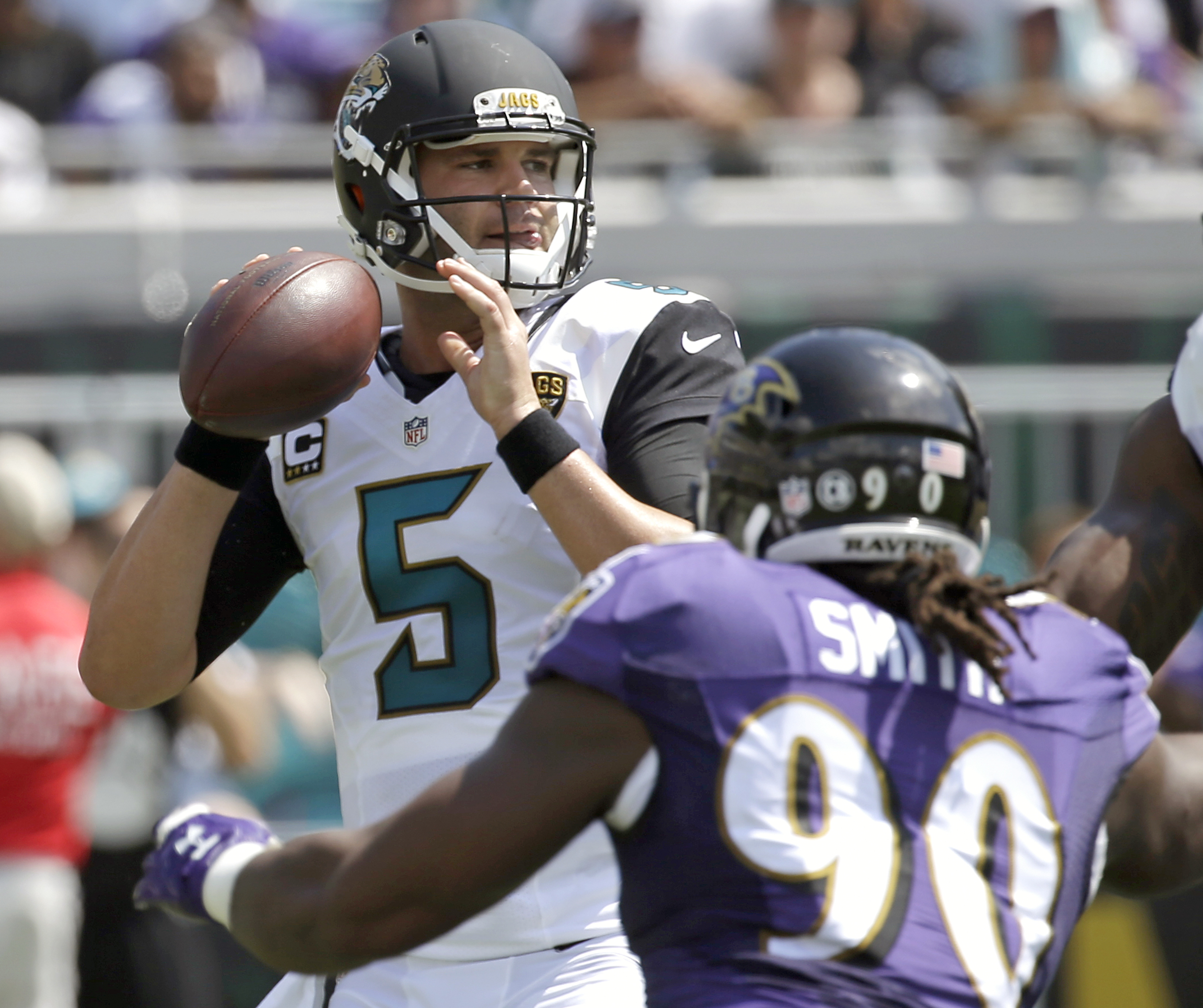 Jacksonville Jaguars quarterback Blake Bortles (5) looks for a receiver as he is pressured by Baltimore Ravens linebacker Za'Darius Smith (90) during the first half of an NFL football game in Jacksonville, Fla., Sunday, Sept. 25, 2016. (AP Photo/John Raou