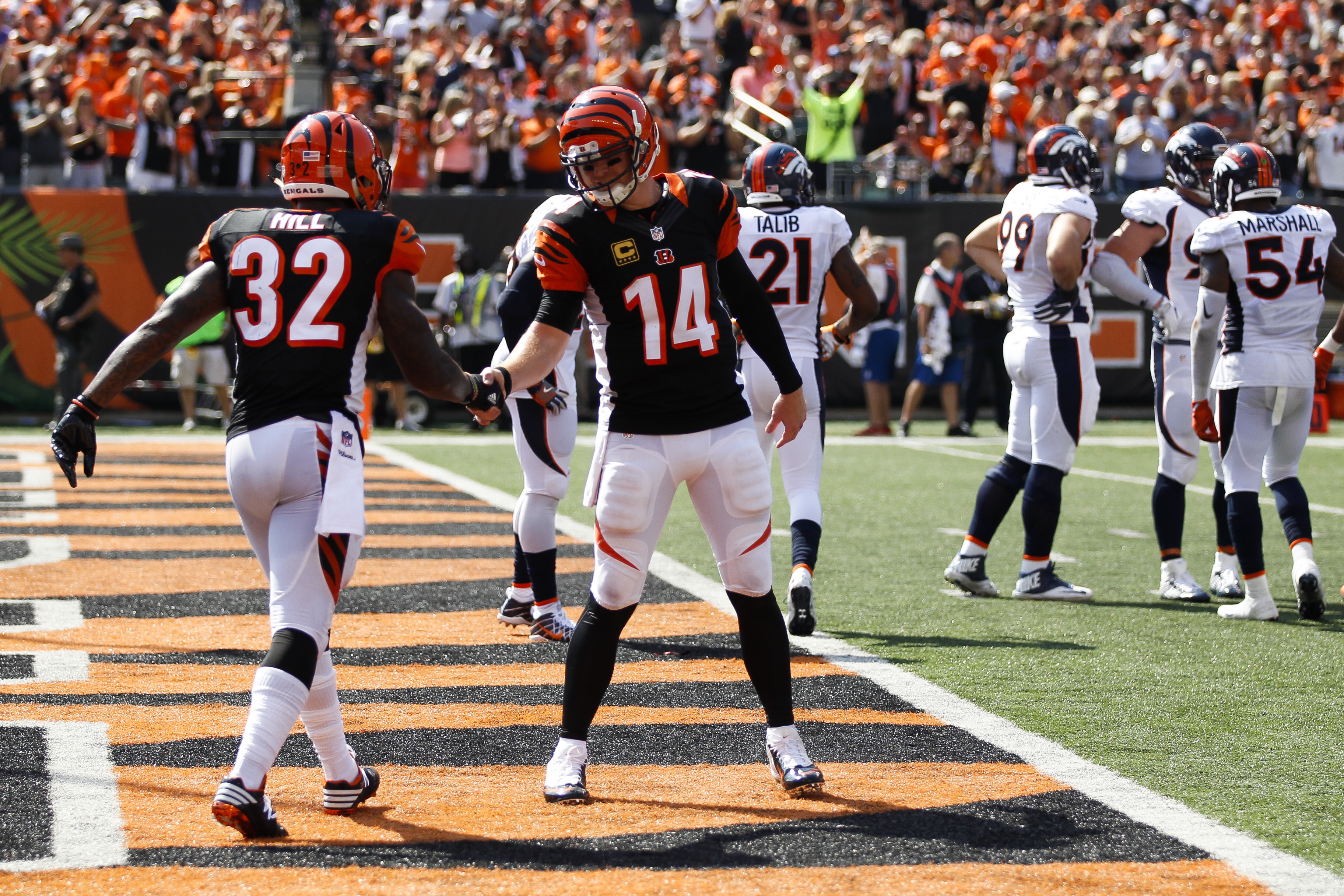 Cincinnati Bengals running back Jeremy Hill (32) celebrates with quarterback Andy Dalton (14) after scoring a touchdown during the first half of an NFL football game against the Denver Broncos, Sunday, Sept. 25, 2016, in Cincinnati. (AP Photo/Gary Landers