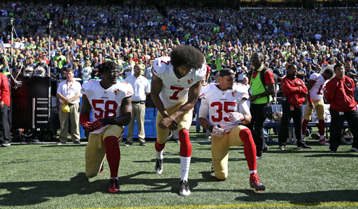 San Francisco 49ers Eli Harold (58), Colin Kaepernick (7) and Eric Reid (35) drop to a kneeling position at the beginning of the national anthem before an NFL football game against the Seattle Seahawks, Sunday, Sept. 25, 2016, in Seattle. (AP Photo/Ted S.