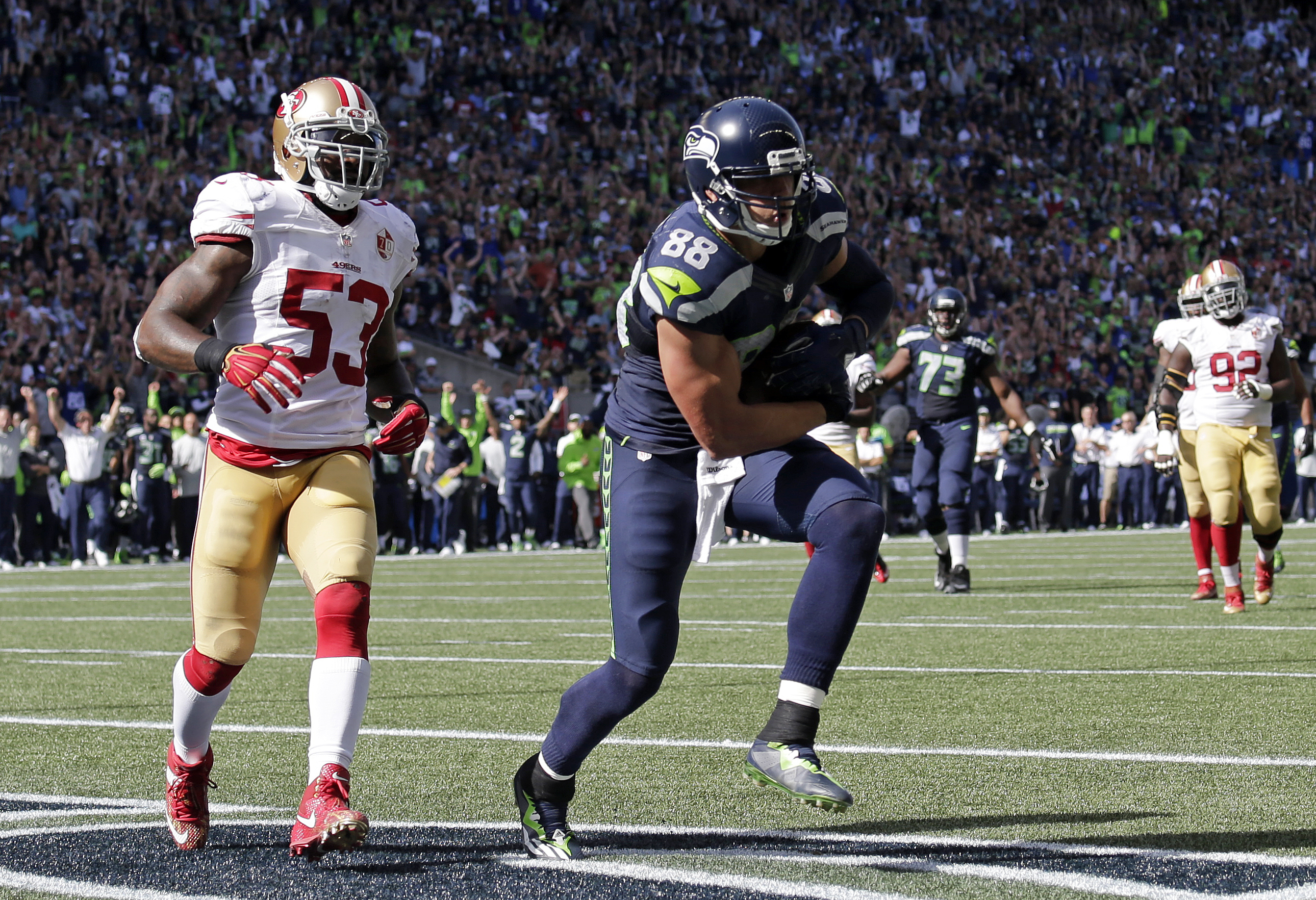 Seattle Seahawks' Jimmy Graham (88) scores a touchdown in front of San Francisco 49ers'n NaVorro Bowman in the first half of an NFL football game, Sunday, Sept. 25, 2016, in Seattle. (AP Photo/John Froschauer)