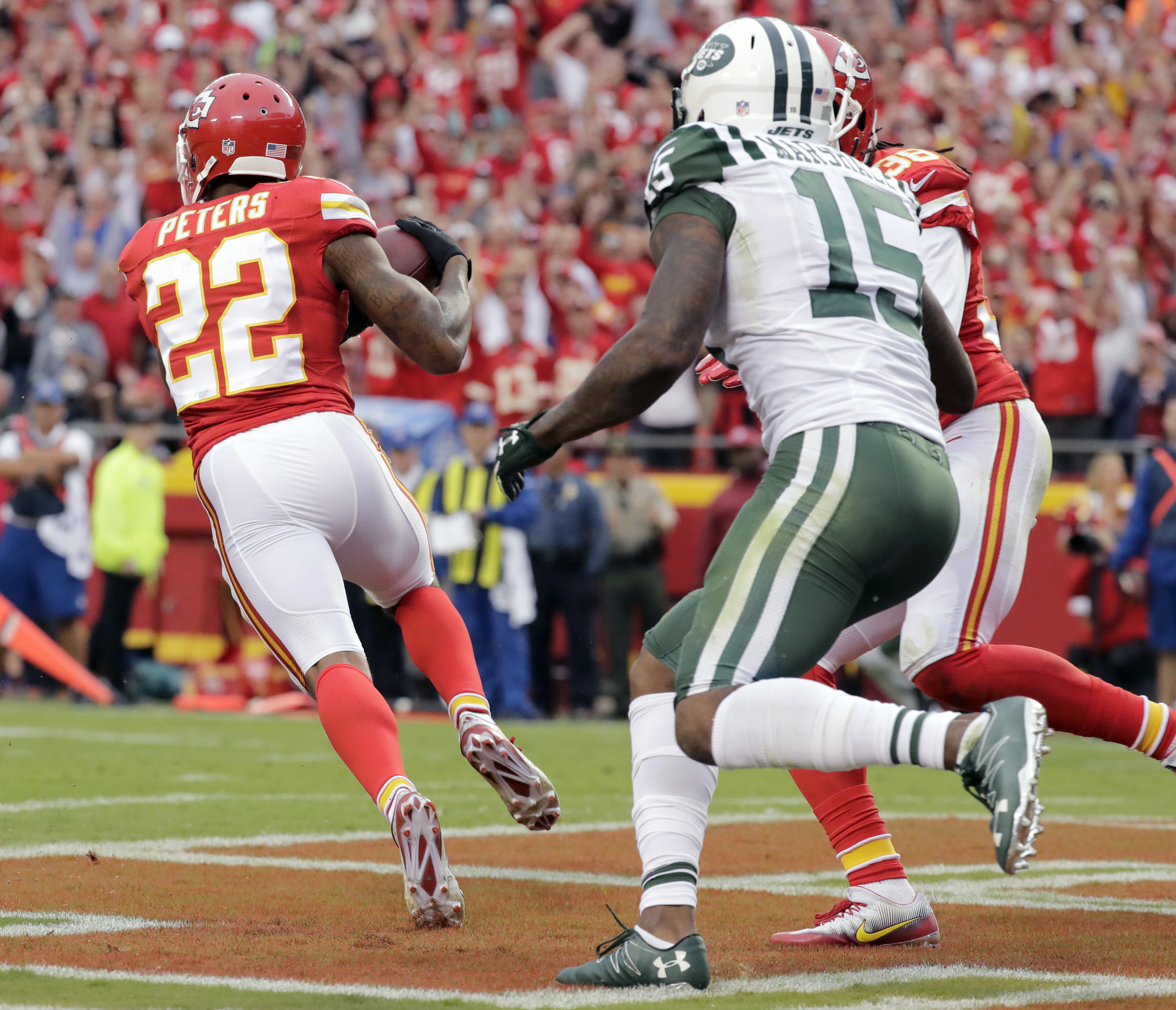 Kansas City Chiefs defensive back Marcus Peters (22) intercepts a pass in front of New York Jets wide receiver Brandon Marshall (15) in the end zone, during the second half of an NFL football game in Kansas City, Mo., Sunday, Sept. 25, 2016. (AP Photo/Cha