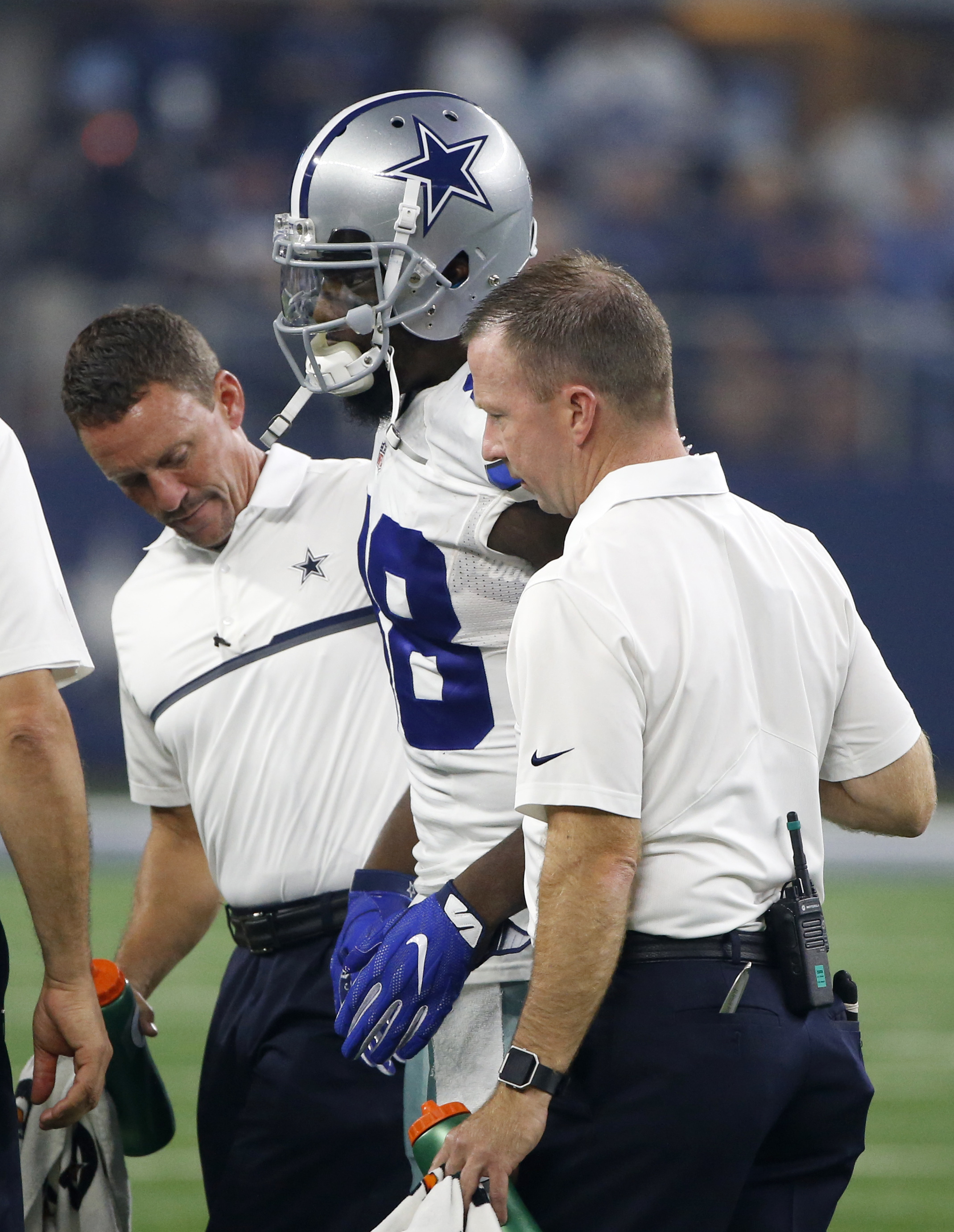 Dallas Cowboys wide receiver Dez Bryant, center, is helped off the field after suffering an unknown injury in the first half of an NFL football game against the Chicago Bears, Sunday, Sept. 25, 2016, in Arlington, Texas. (AP Photo/Ron Jenkins)
