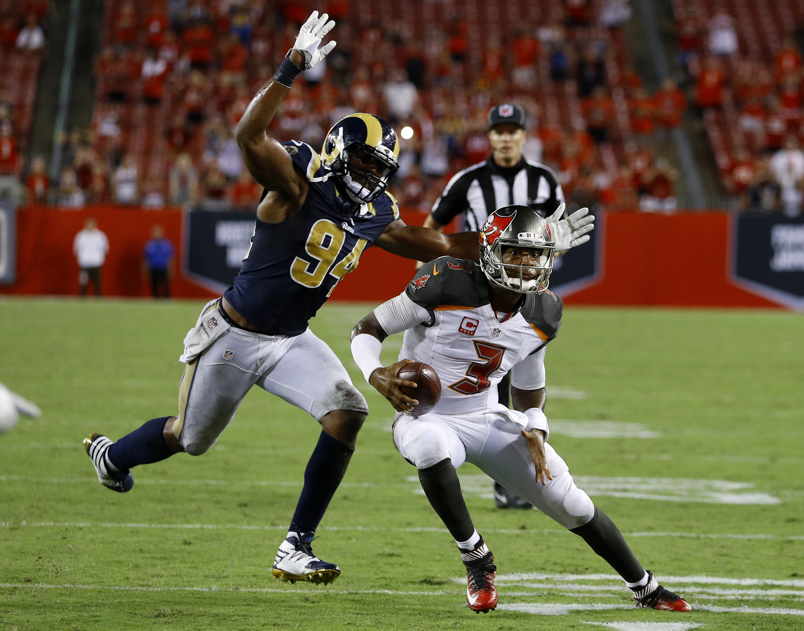 Tampa Bay Buccaneers quarterback Jameis Winston (3) is chased by Los Angeles Rams defensive end Robert Quinn (94) during the final play of an NFL football game Sunday, Sept. 25, 2016, in Tampa, Fla. The Rams defeated the Buccaneers 37-32. (AP Photo/Scott