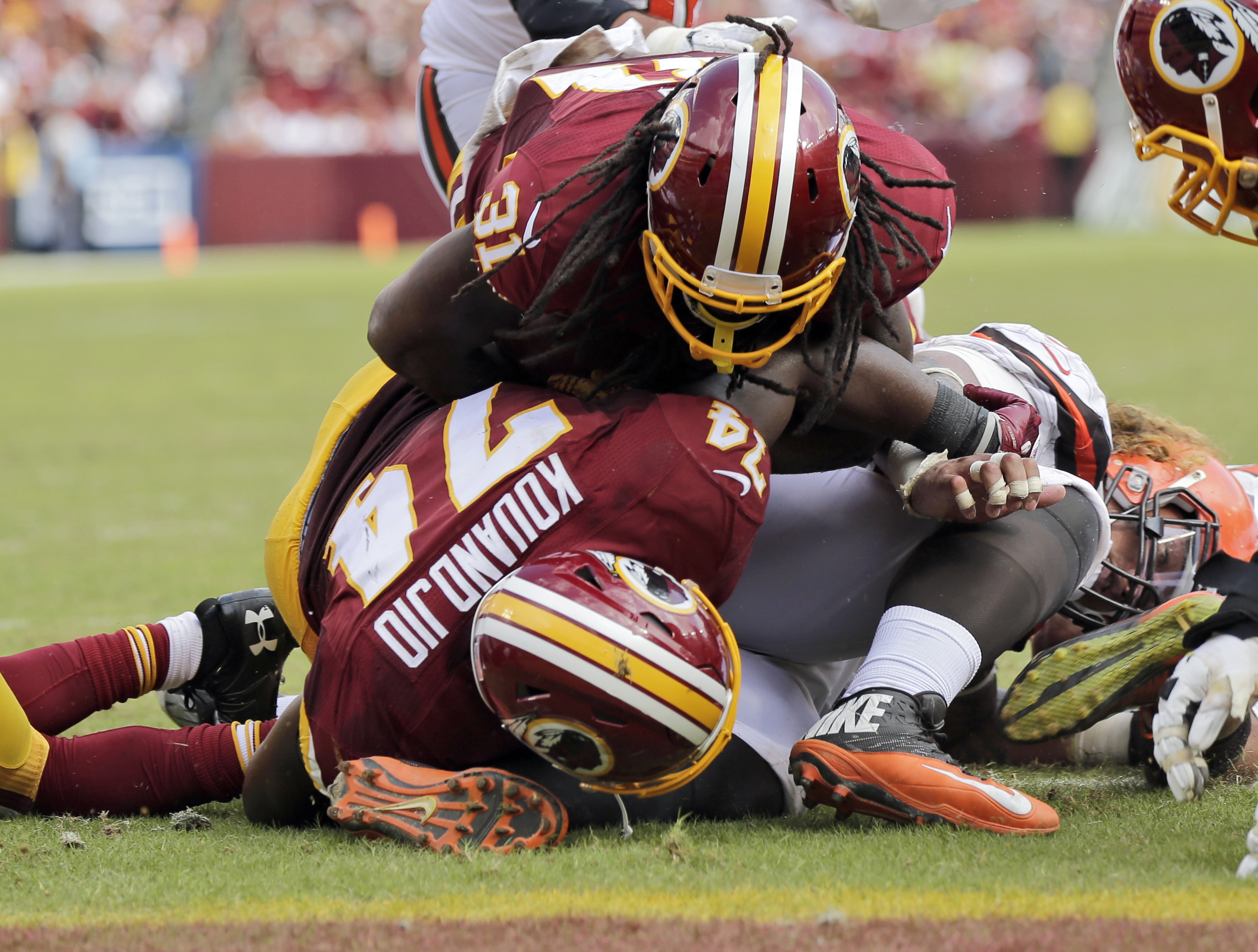 Washington Redskins running back Matt Jones (31) goes over offensive guard Arie Kouandjio (74) and Cleveland Browns nose tackle Danny Shelton for a touchdown during the second half of an NFL football game Sunday, Oct. 2, 2016, in Landover, Md. (AP Photo/M