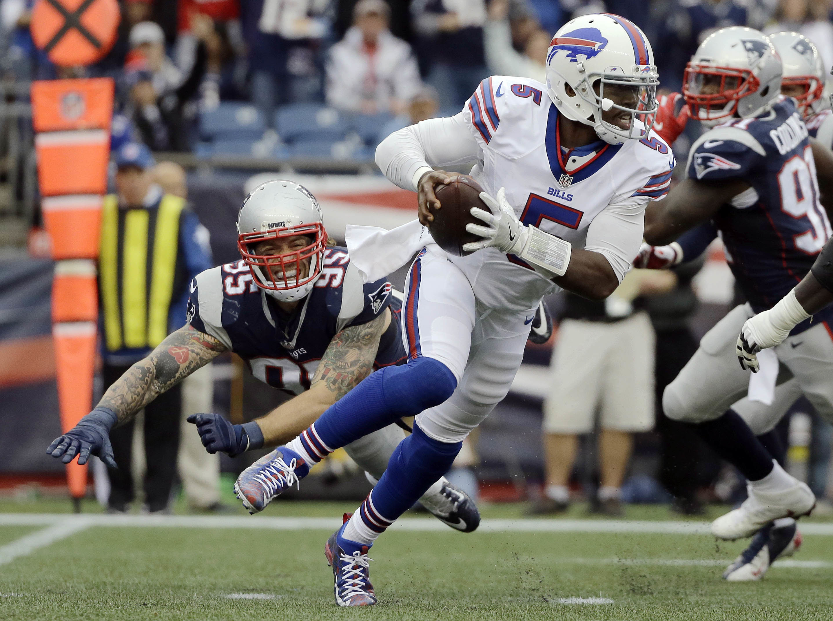 Buffalo Bills quarterback Tyrod Taylor (5) scrambles away from New England Patriots defenders Chris Long, left, and Jamie Collins, right, during the second half of an NFL football game Sunday, Oct. 2, 2016, in Foxborough, Mass. (AP Photo/Elise Amendola)