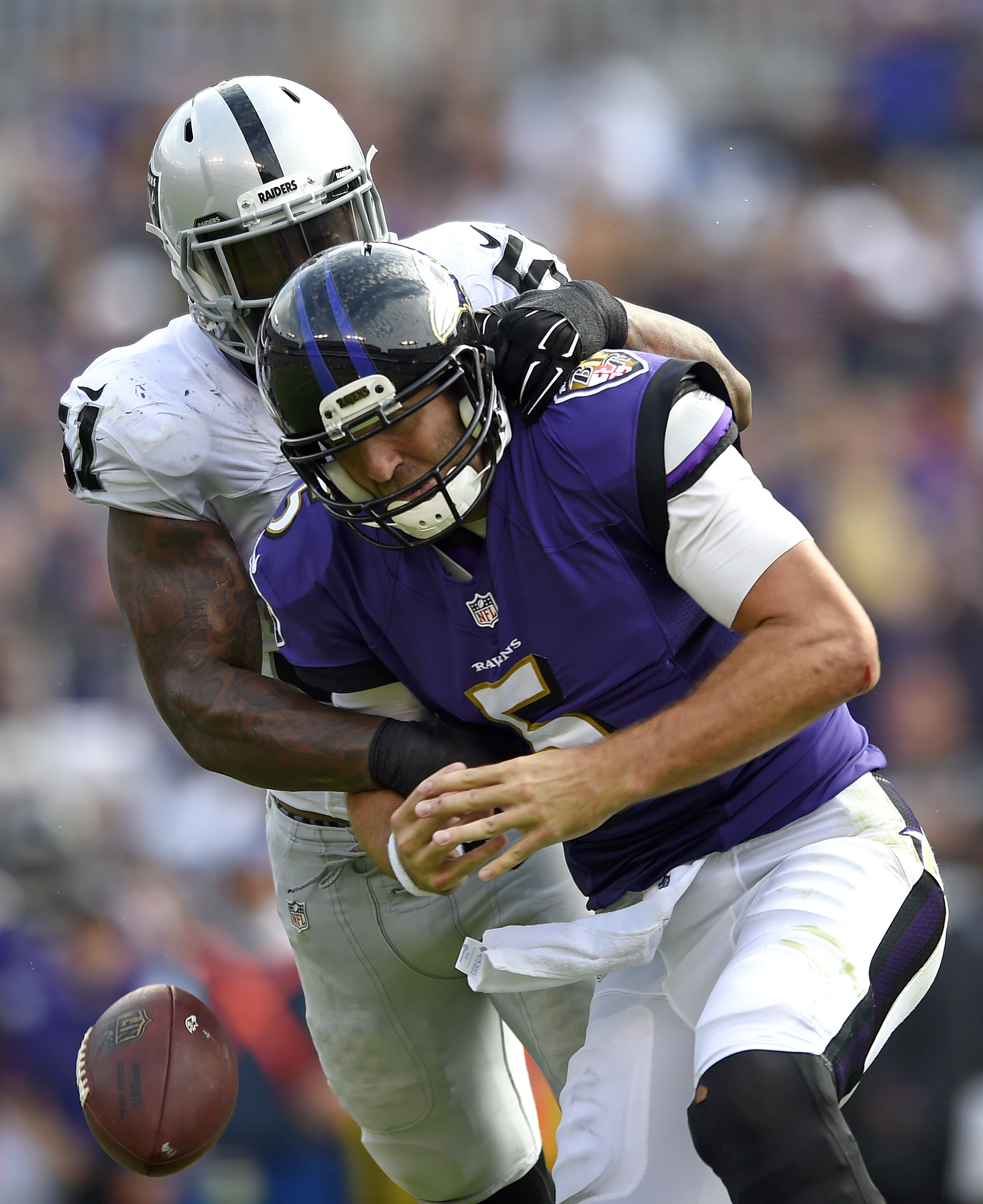 Baltimore Ravens quarterback Joe Flacco (5) fumbles the ball as he is sacked by Oakland Raiders outside linebacker Bruce Irvin in the second half of an NFL football game, Sunday, Oct. 2, 2016, in Baltimore. Oakland recovered the ball on the play. (AP Phot