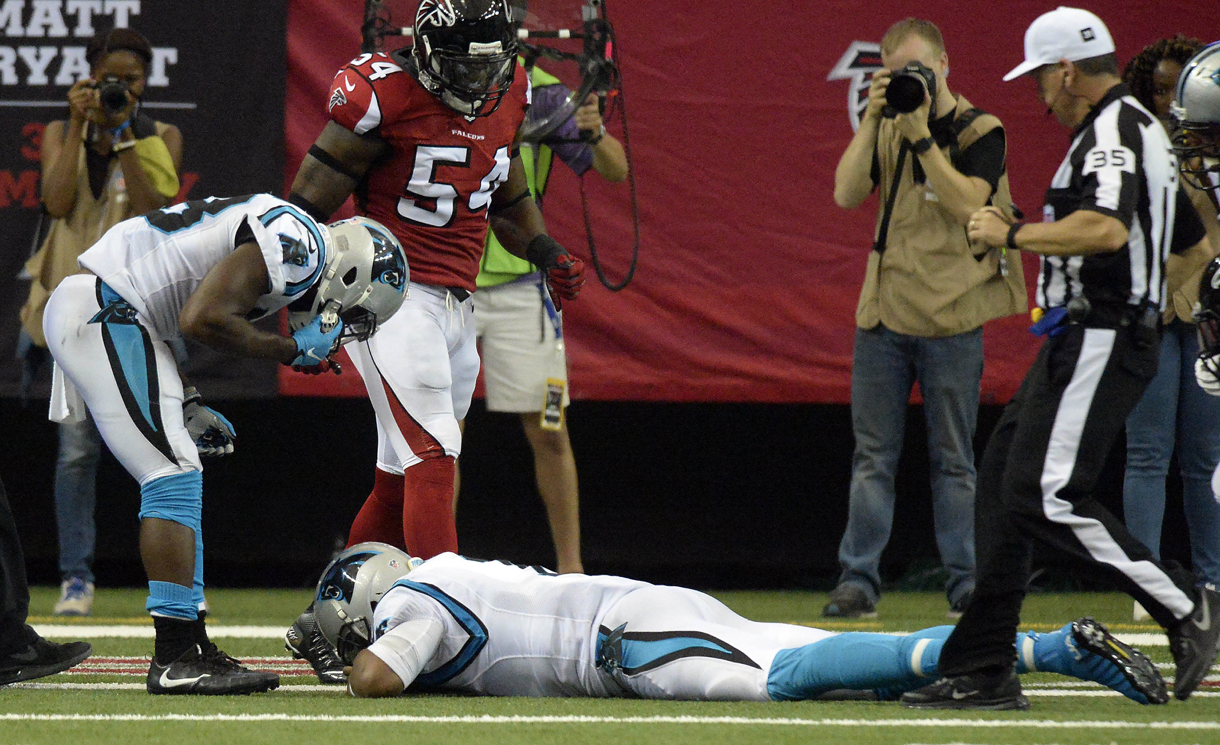 Carolina Panthers quarterback Cam Newton lies on the turf as running back Fozzy Whittaker (43) referee John Hussey (35), and Atlanta Falcons defensive end O'Brien Schofield (54) look down at him after a hit during a two-point conversion in the second half