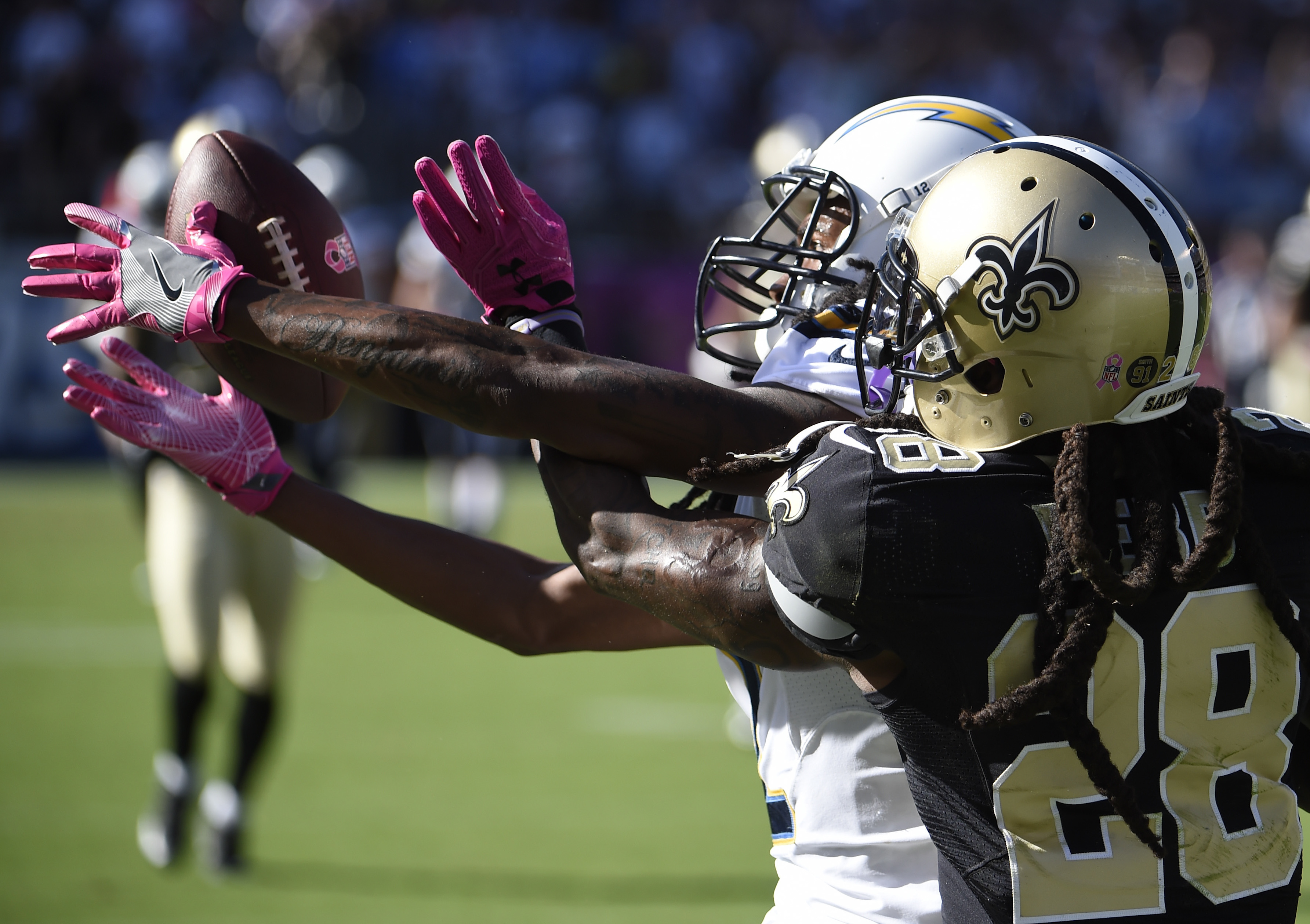 San Diego Chargers wide receiver Travis Benjamin, second from right, tries to haul in a reception as New Orleans Saints defensive back B.W. Webb (28) defends during the second half of an NFL football game, Sunday, Oct. 2, 2016, in San Diego. (AP Photo/Len