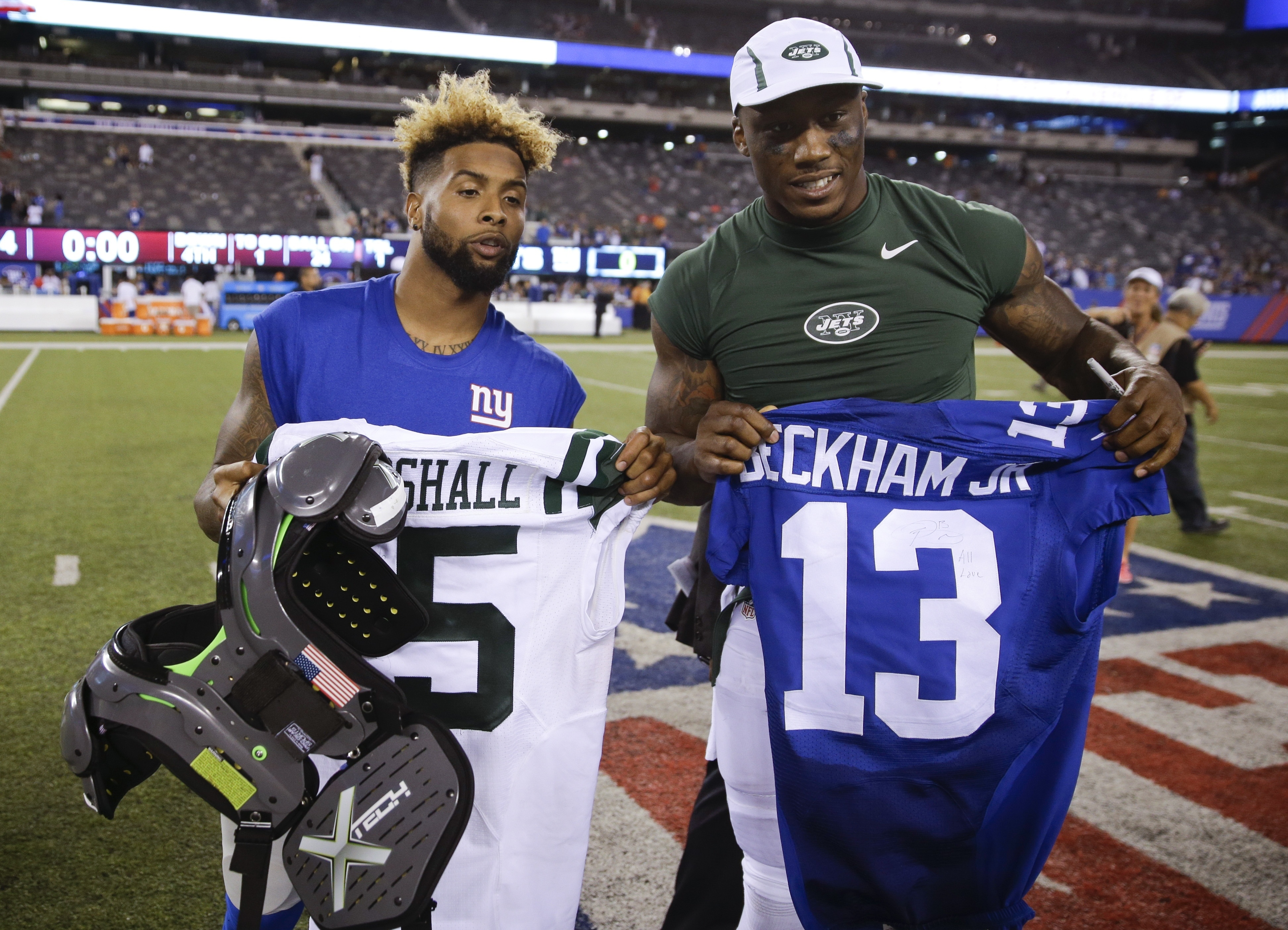 FILE - In tihs Aug. 29, 2015, file photo, New York Giants wide receiver Odell Beckham, left, and New York Jets wide receiver Brandon Marshall, right, pose for photographs after exchanging jerseys after a preseason NFL football game in East Rutherford, N.J