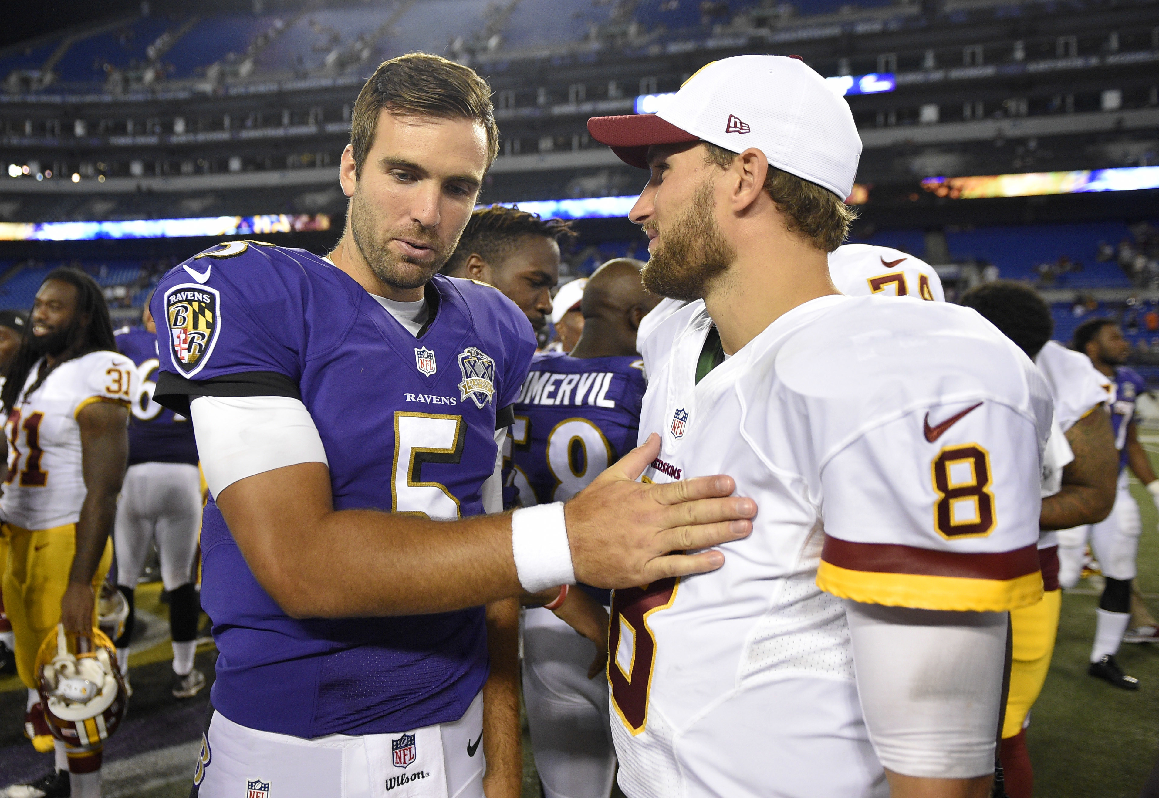 FILE - In this Aug. 29, 2015, file photo, Baltimore Ravens quarterback Joe Flacco, left, chats with Washington Redskins quarterback Kirk Cousins after a preseason NFL football game in Baltimore. If the cornerstone of a great rivalry is proximity between t