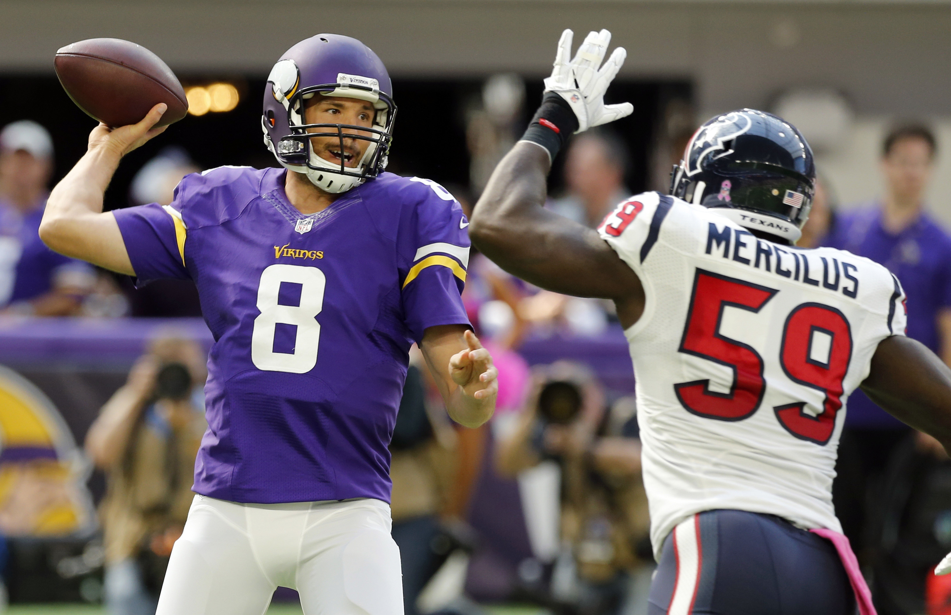 Minnesota Vikings quarterback Sam Bradford (8) throws a pass over Houston Texans outside linebacker Whitney Mercilus, right, during the first half of an NFL football game Sunday, Oct. 9, 2016, in Minneapolis. (AP Photo/Jim Mone)