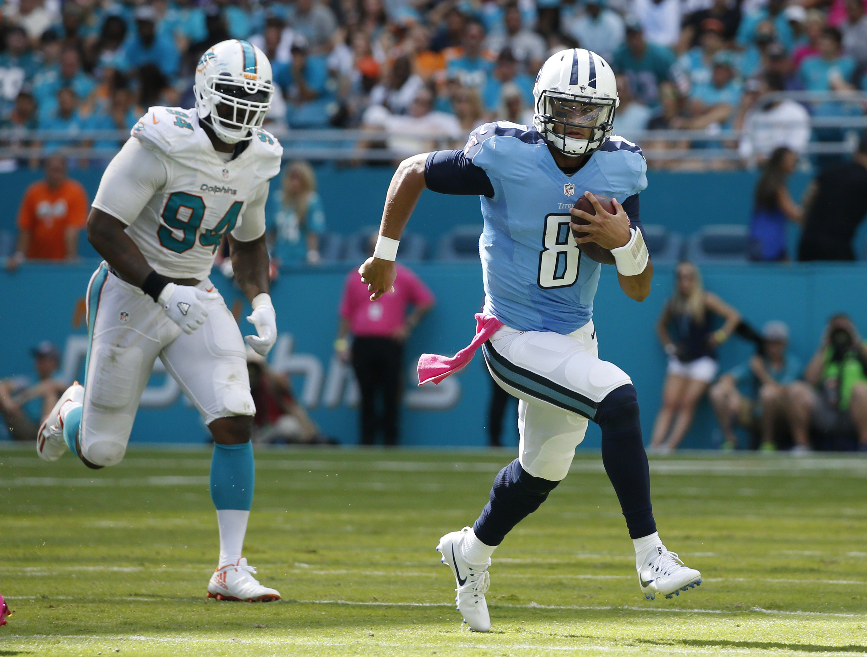 Tennessee Titans quarterback Marcus Mariota (8) runs with the ball ahead of Miami Dolphins defensive end Mario Williams (94), during the second half of an NFL football game, Sunday, Oct. 9, 2016, in Miami Gardens, Fla. Mariota threw for three touchdowns a