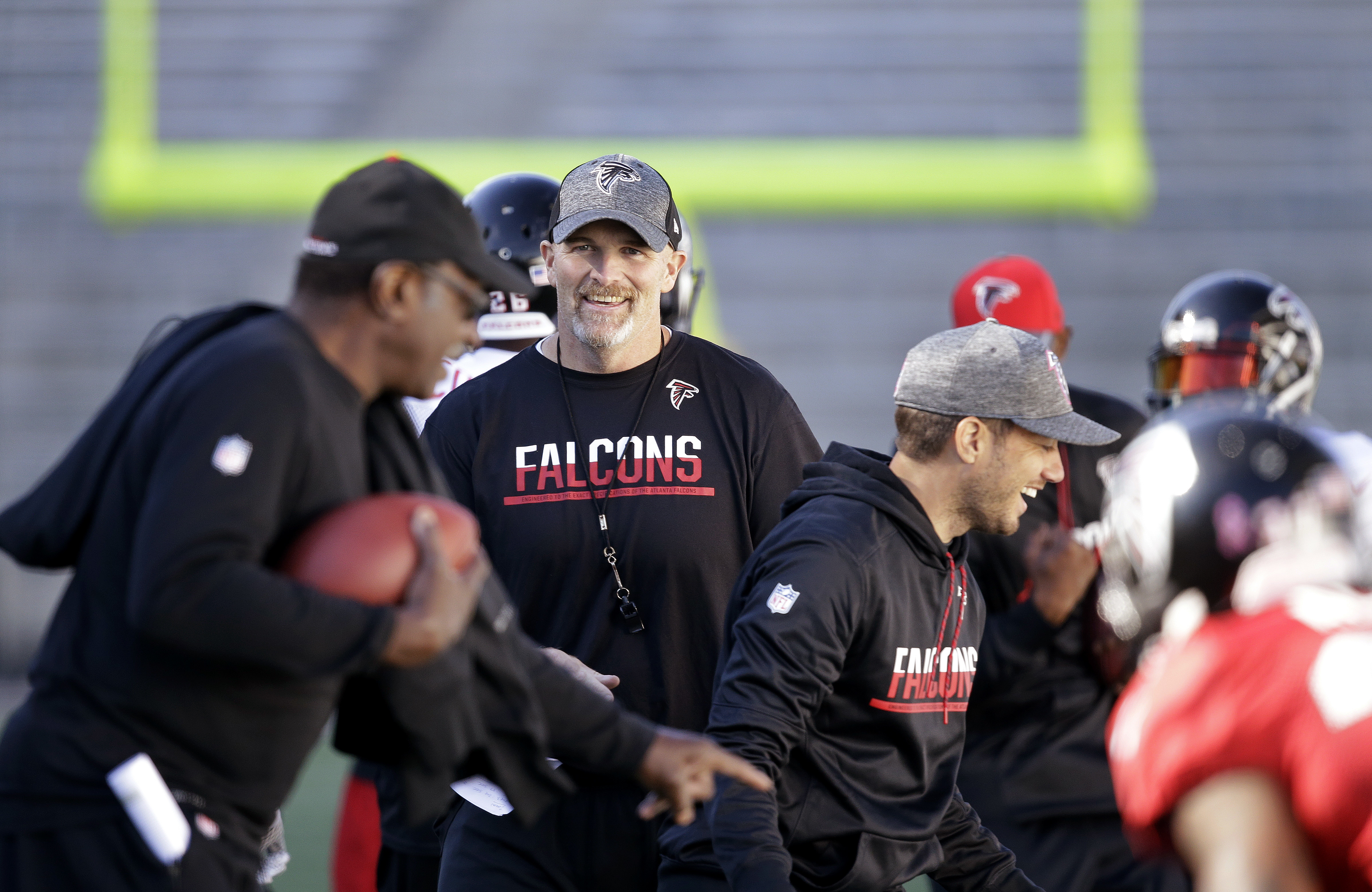 Atlanta Falcons coach Dan Quinn smiles as he watches the team practice at the University of Washington on Wednesday, Oct. 12, 2016, in Seattle. Rather than head home, the team traveled directly to Seattle after its football game Sunday in Denver, ahead of