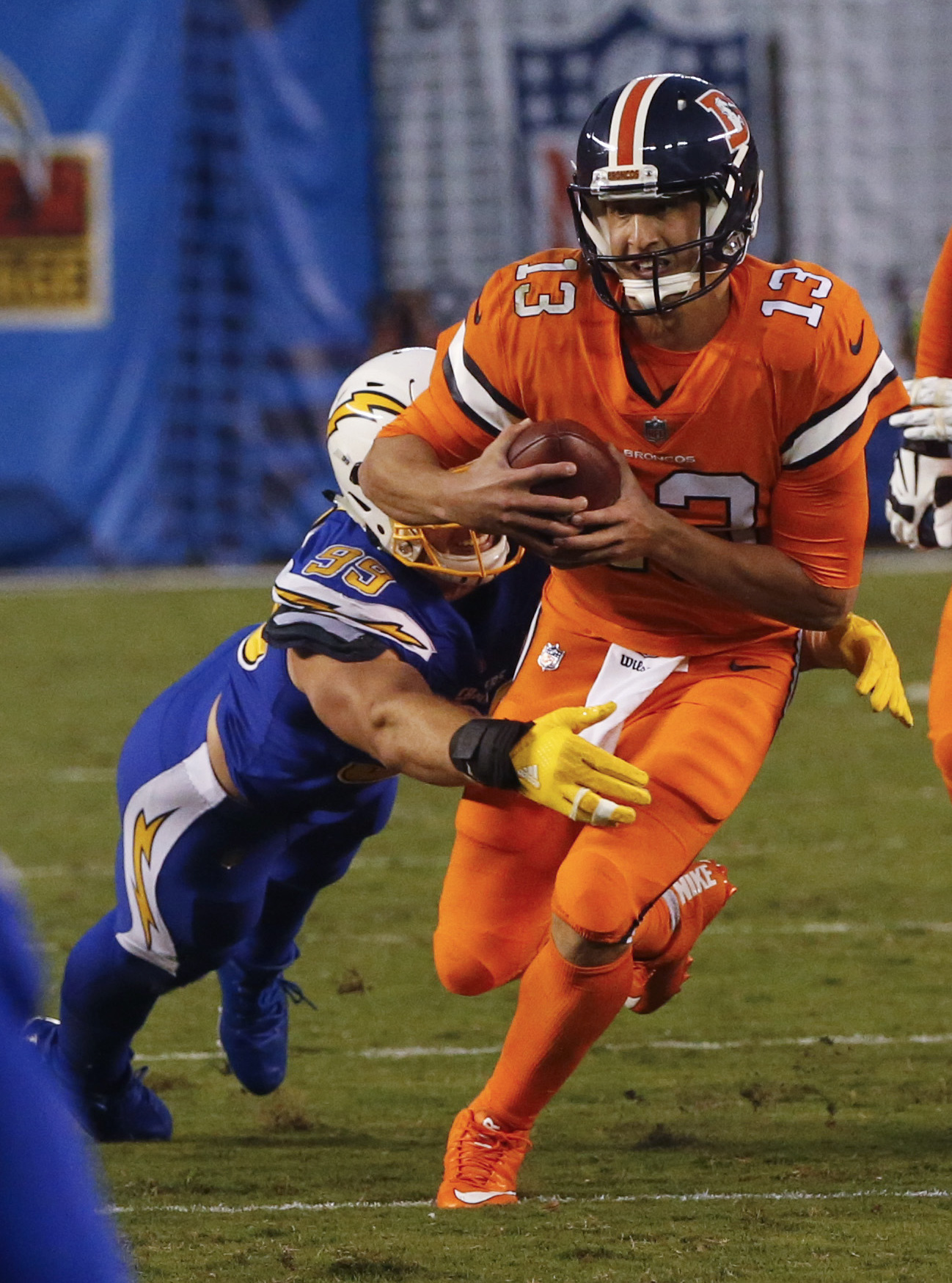 Denver Broncos quarterback Trevor Siemian (13) is brought down by San Diego Chargers defensive end Joey Bosa during the first half of an NFL football game Thursday, Oct. 13, 2016, in San Diego. (AP Photo/Lenny Ignelzi)