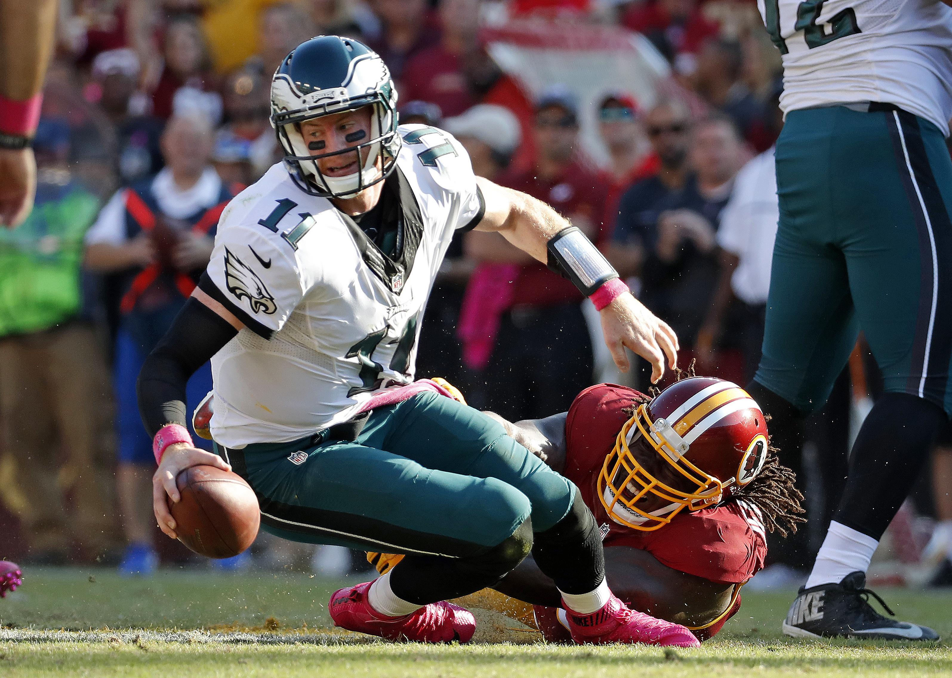 Philadelphia Eagles quarterback Carson Wentz, left, is sacked by Washington Redskins defensive end Ricky Jean Francois in the second half of an NFL football game, Sunday, Oct. 16, 2016, in Landover, Md. Washington won 27-20. (AP Photo/Alex Brandon)