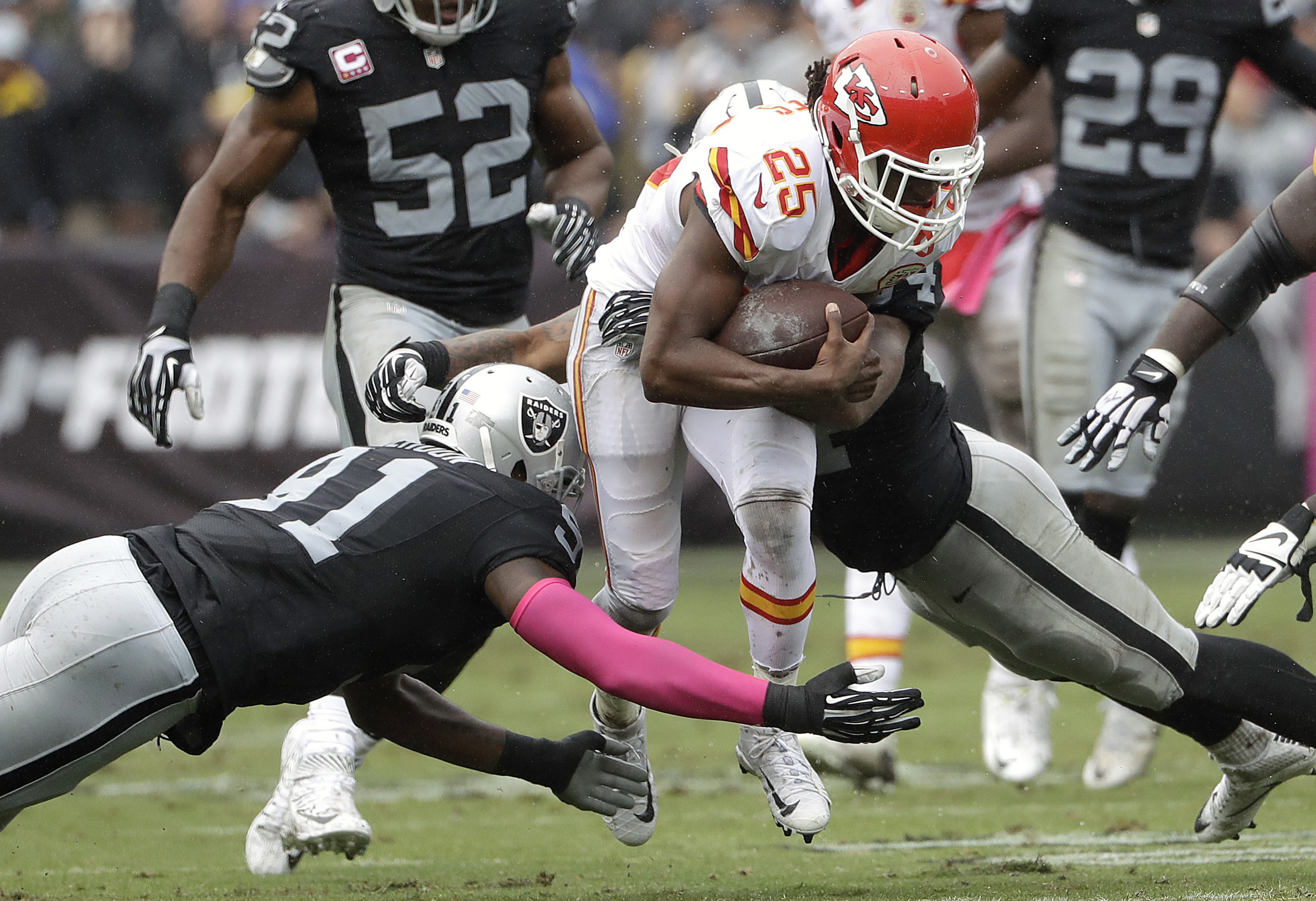 Kansas City Chiefs running back Jamaal Charles (25) runs against Oakland Raiders linebacker Shilique Calhoun, left, and linebacker Perry Riley Jr. during the first half of an NFL football game in Oakland, Calif., Sunday, Oct. 16, 2016. (AP Photo/Marcio Jo