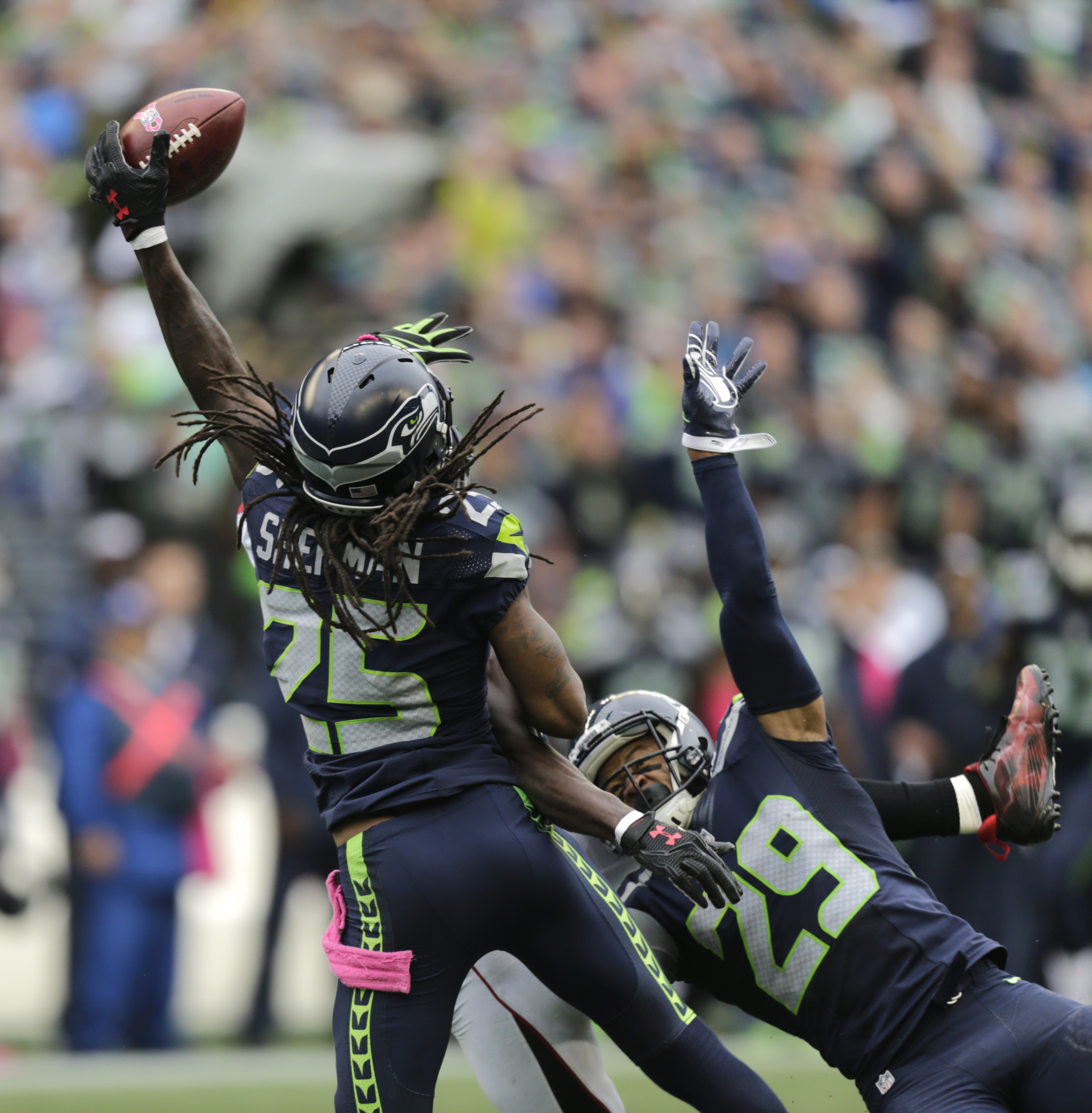 Seattle Seahawks cornerback Richard Sherman (25) and Earl Thomas (29) break up a pass intended for Atlanta Falcons wide receiver Julio Jones (obscured) in the second half of an NFL football game, Sunday, Oct. 16, 2016, in Seattle. The Seahawks defeated th