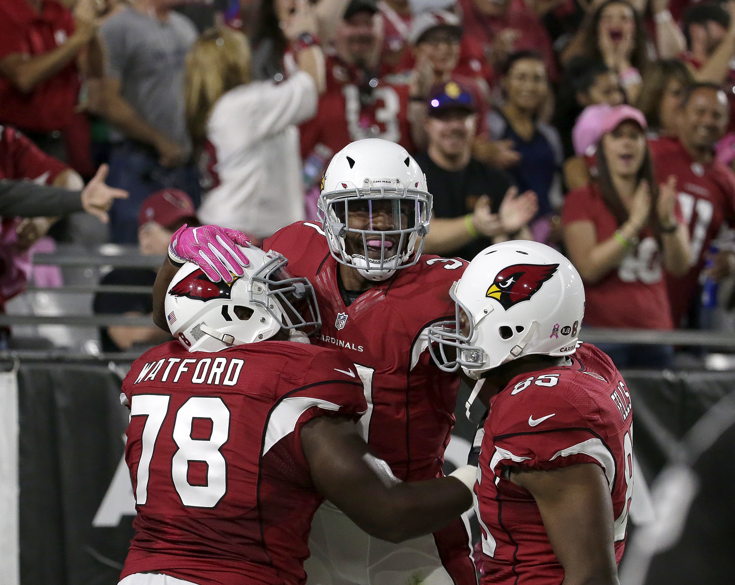 Arizona Cardinals running back David Johnson, center, celebrates his touchdown run with guard Earl Watford (78) and tight end Darren Fells (85) during the first half of an NFL football game against the New York Jets, Monday, Oct. 17, 2016, in Glendale, Ar