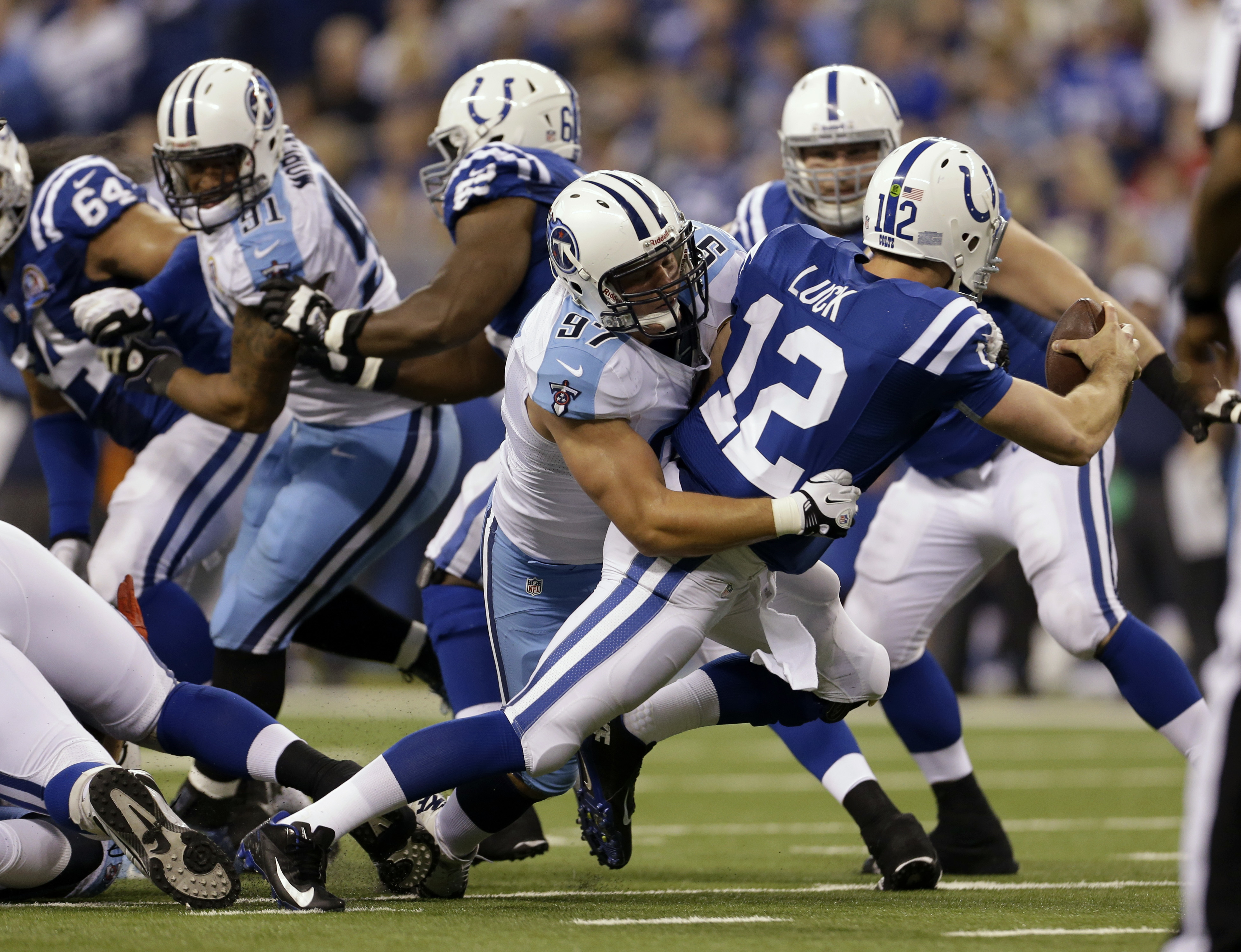 FILE - In this Dec. 2, 2012, file photo, Indianapolis Colts' Andrew Luck (12) is sacked by Tennessee Titans' Karl Klug (97) during the first half of an NFL football game in Indianapolis. The Titans have piled up 12 sacks over the past two games and are am
