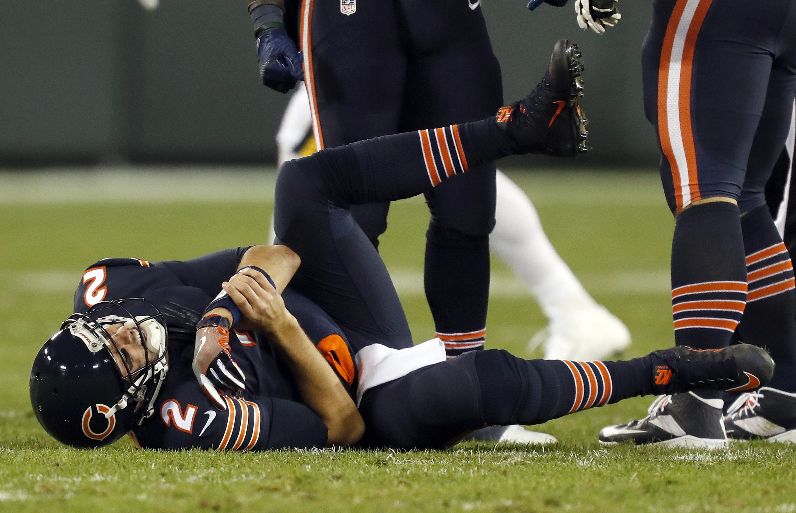 Chicago Bears quarterback Brian Hoyer (2) holds his arm after getting tackled between Green Bay Packers outside linebacker Clay Matthews (52) and outside linebacker Julius Peppers (56) as he throws the ball during the first half of an NFL football game, T