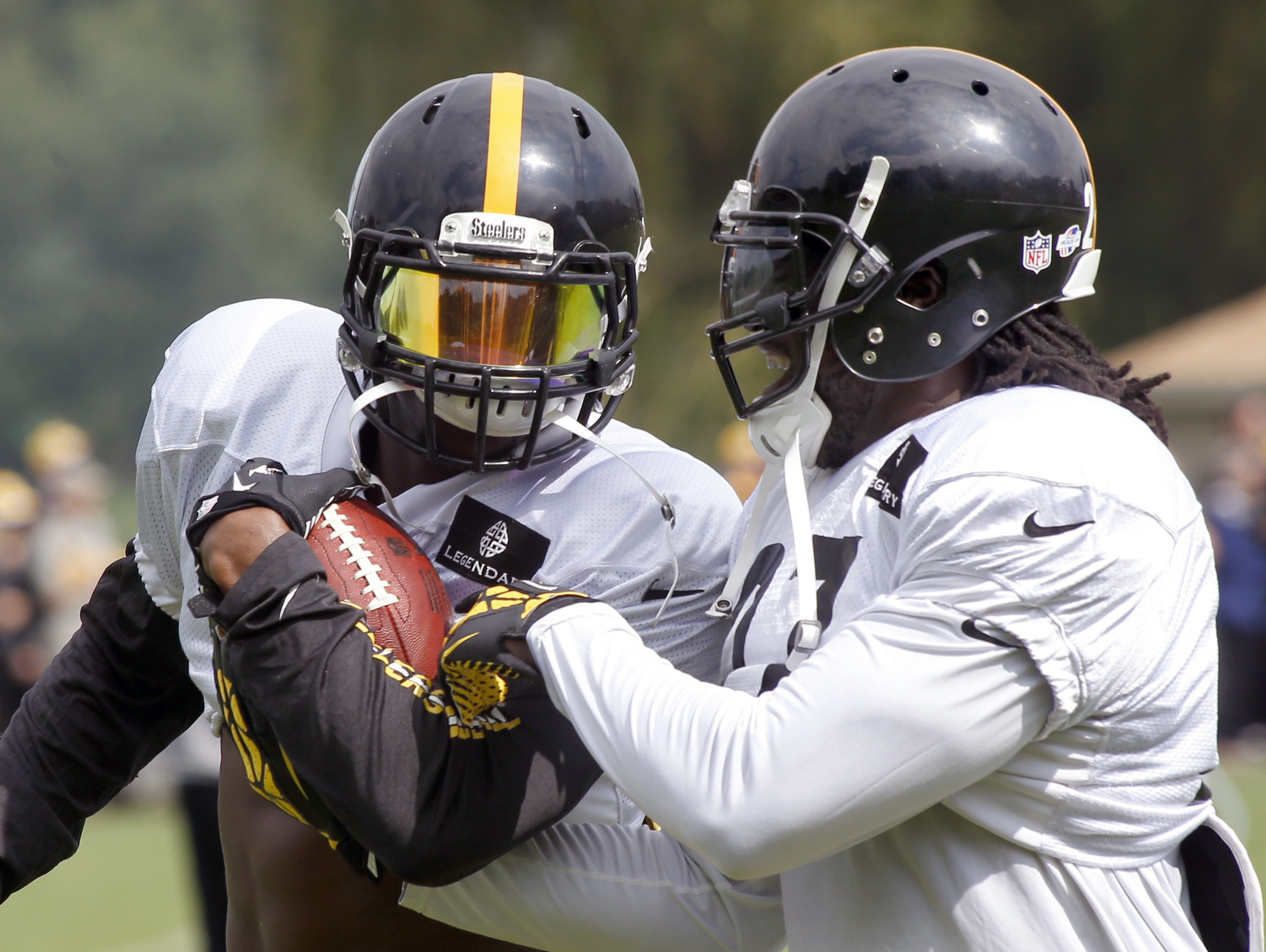 FILE - In this Aug. 13, 2014, file photo, Pittsburgh Steelers running back LeGarrette Blount, right, tries to strip the ball from fellow Steelers running back Le'Veon Bell in a drill during NFL football training camp in Latrobe, Pa. Blount effectively wal