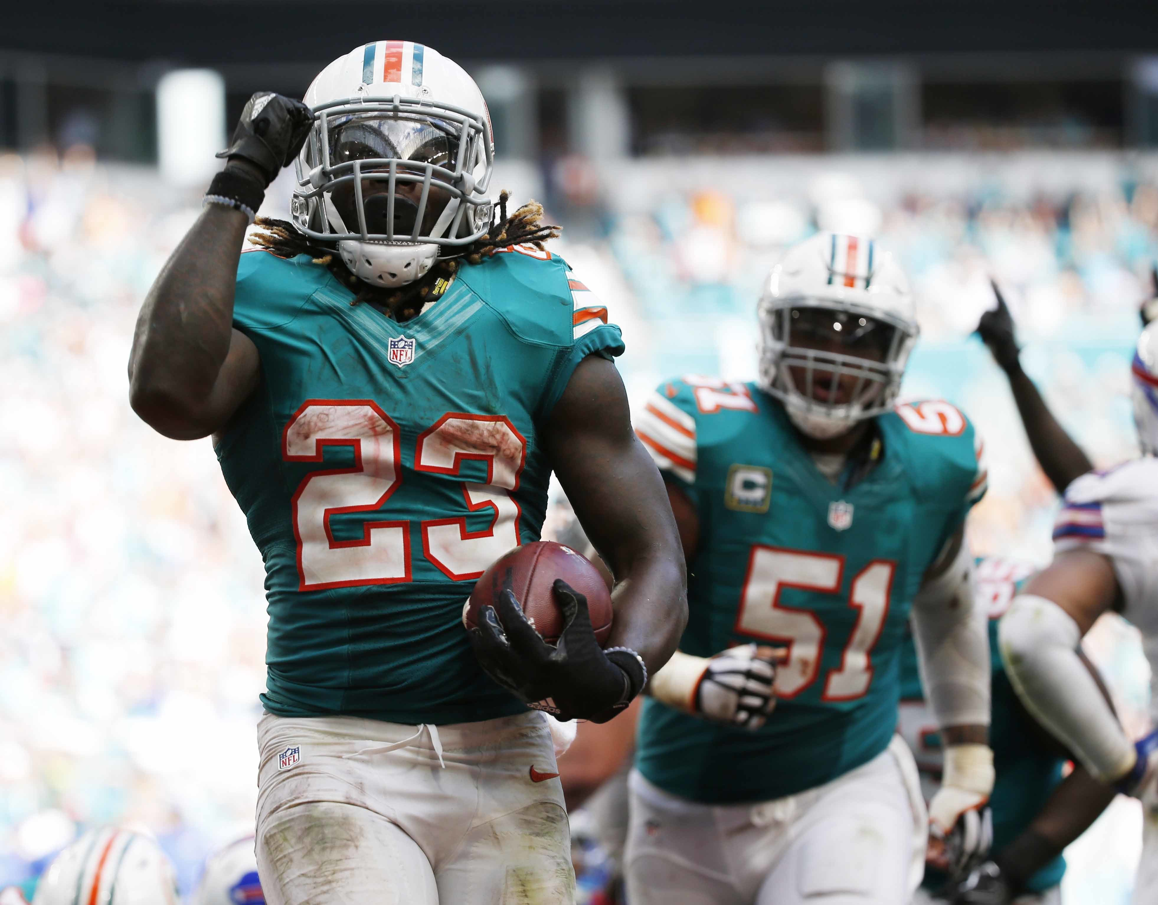Miami Dolphins running back Jay Ajayi (23) celebrates a touchdown during the second half of an NFL football game against the Buffalo Bills, Sunday, Oct. 23, 2016, in Miami Gardens, Fla. To the right is Miami Dolphins center Mike Pouncey (51). (AP Photo/Wi