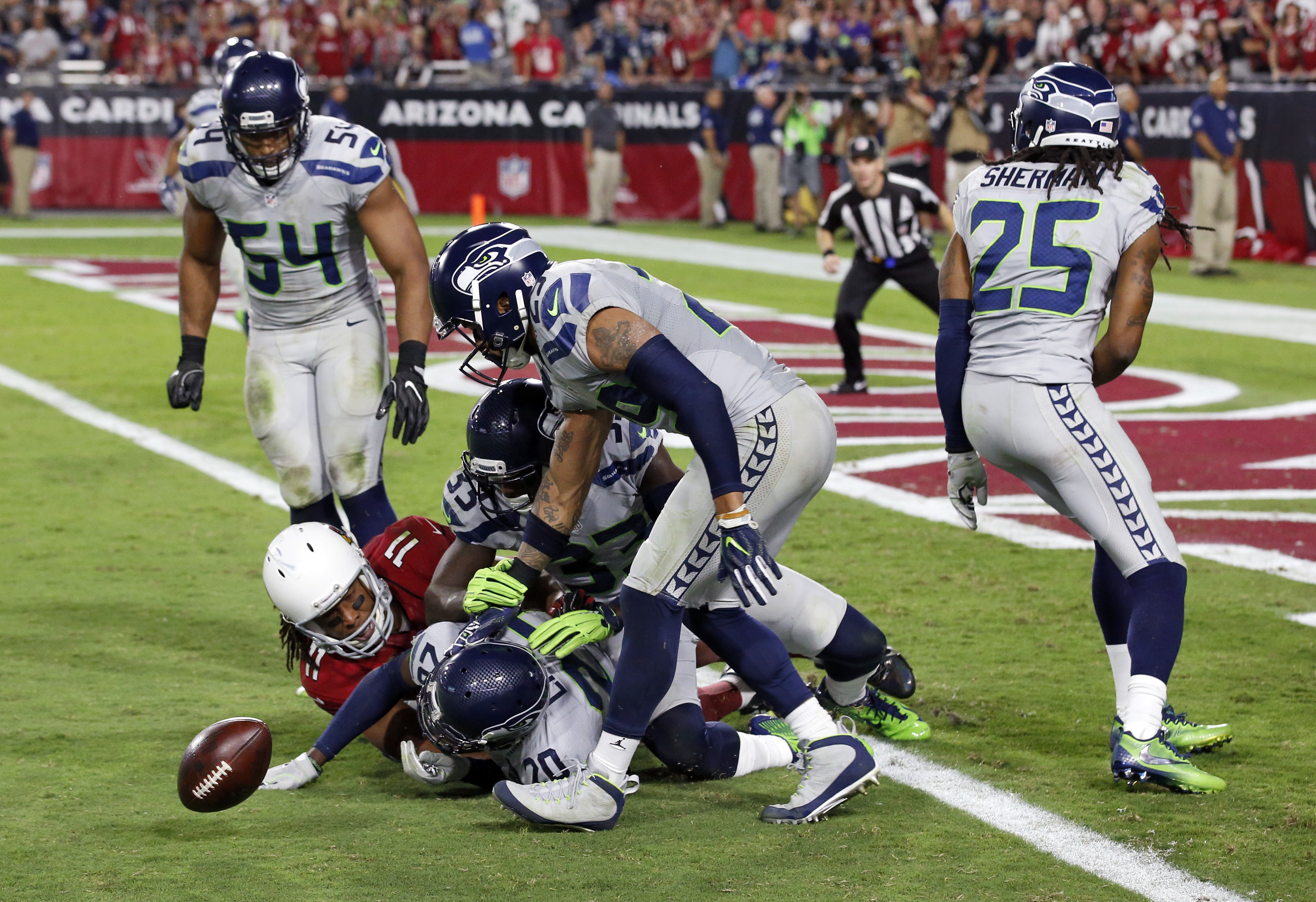 Seattle Seahawks cornerback Richard Sherman (25), free safety Earl Thomas (29), middle linebacker Bobby Wagner (54) strong safety Kelcie McCray (33) and cornerback Jeremy Lane (20) knock the ball away from Arizona Cardinals wide receiver Larry Fitzgerald