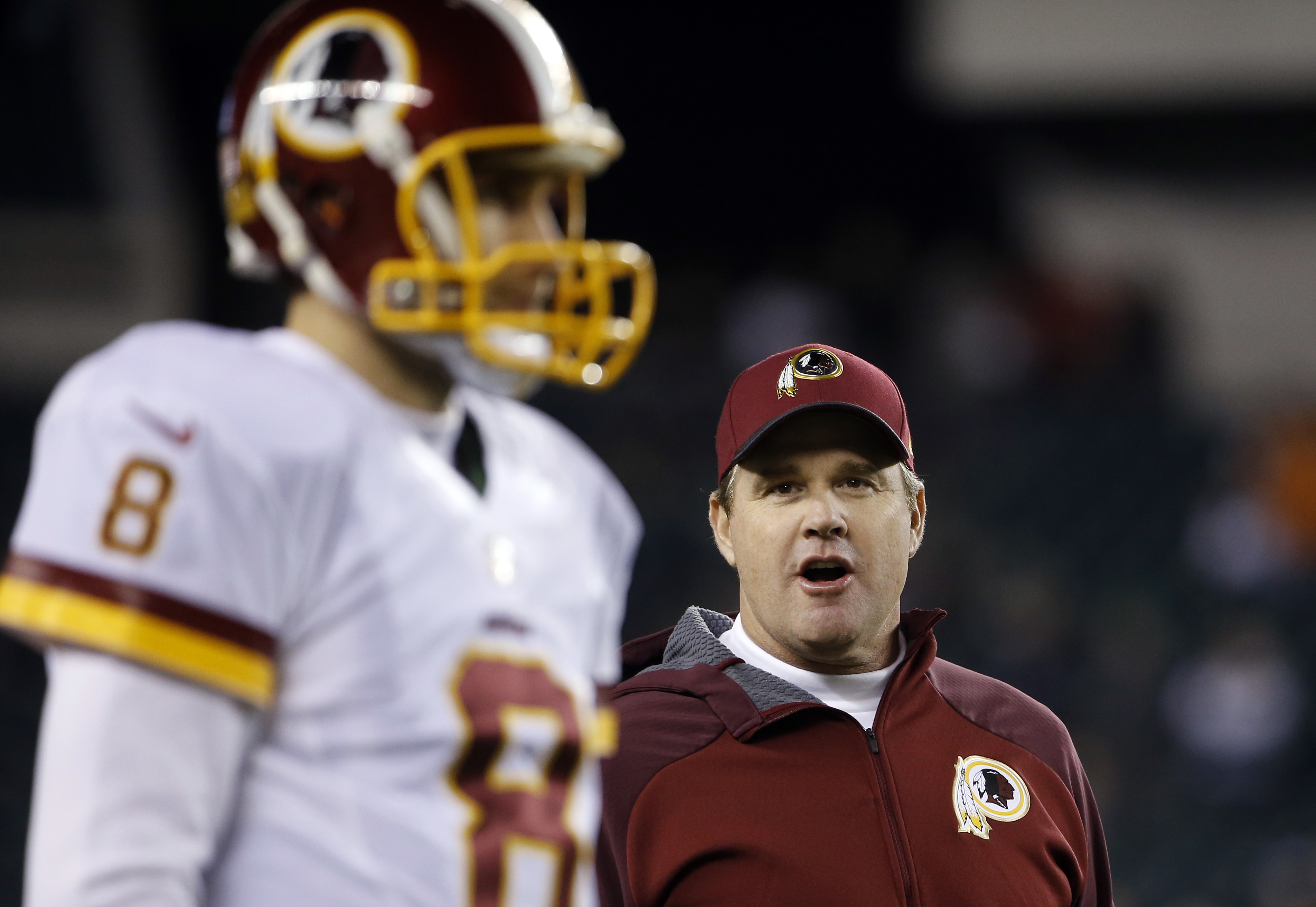 FILE - In this Dec. 26, 2015, file photo, Washington Redskins head coach Jay Gruden, right, watches quarterback Kirk Cousins warm up before an NFL football game against the Philadelphia Eagles in Philadelphia. Gruden is excited to face his former team in