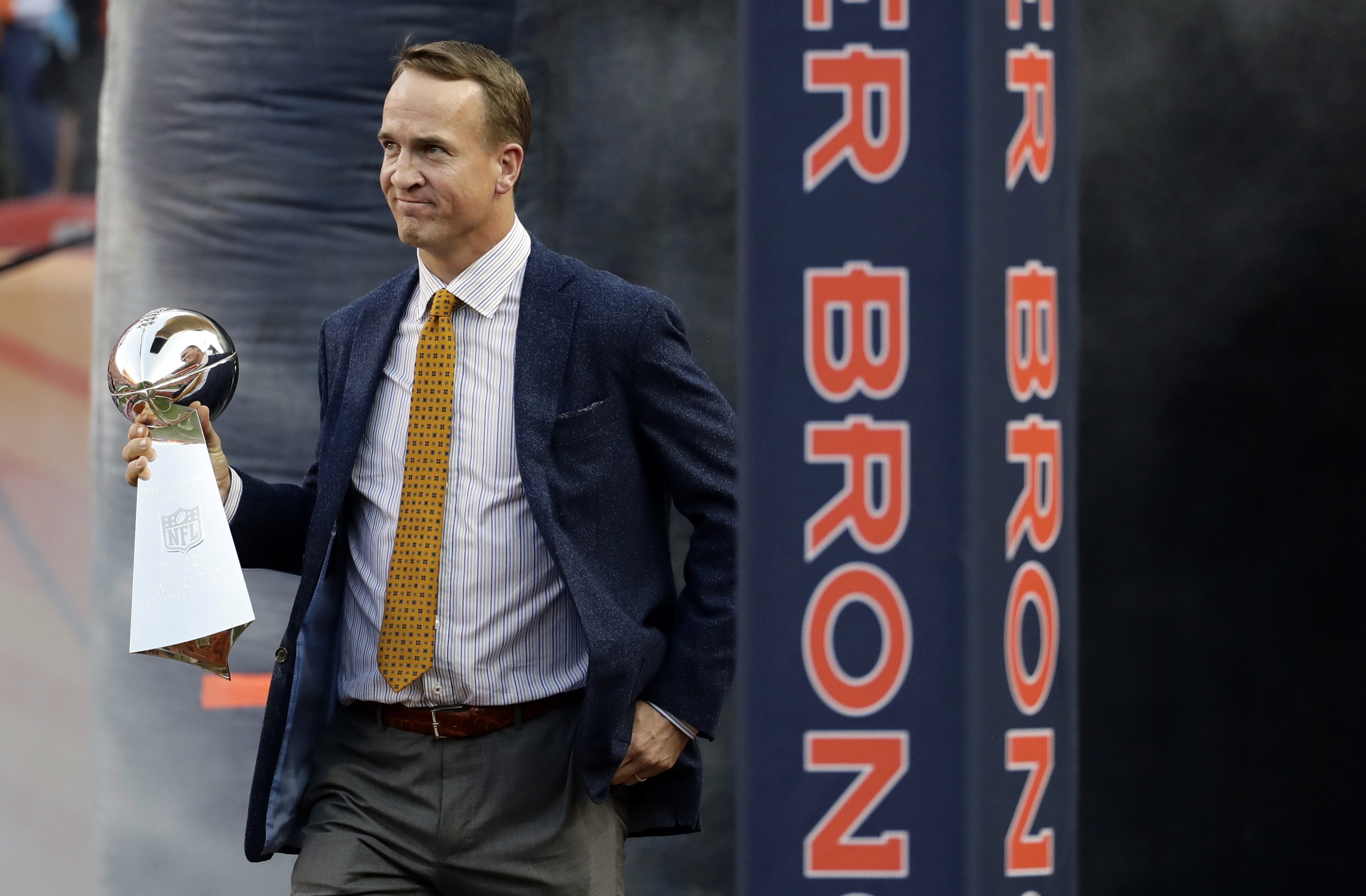 FILE - In this Sept. 8, 2016, file photo, former Denver Broncos quarterback Peyton Manning carries the Vince Lombardi Trophy from Super Bowl 50 onto the field prior to an NFL football game against the Carolina Panthers in Denver. Manning has gone to TV co